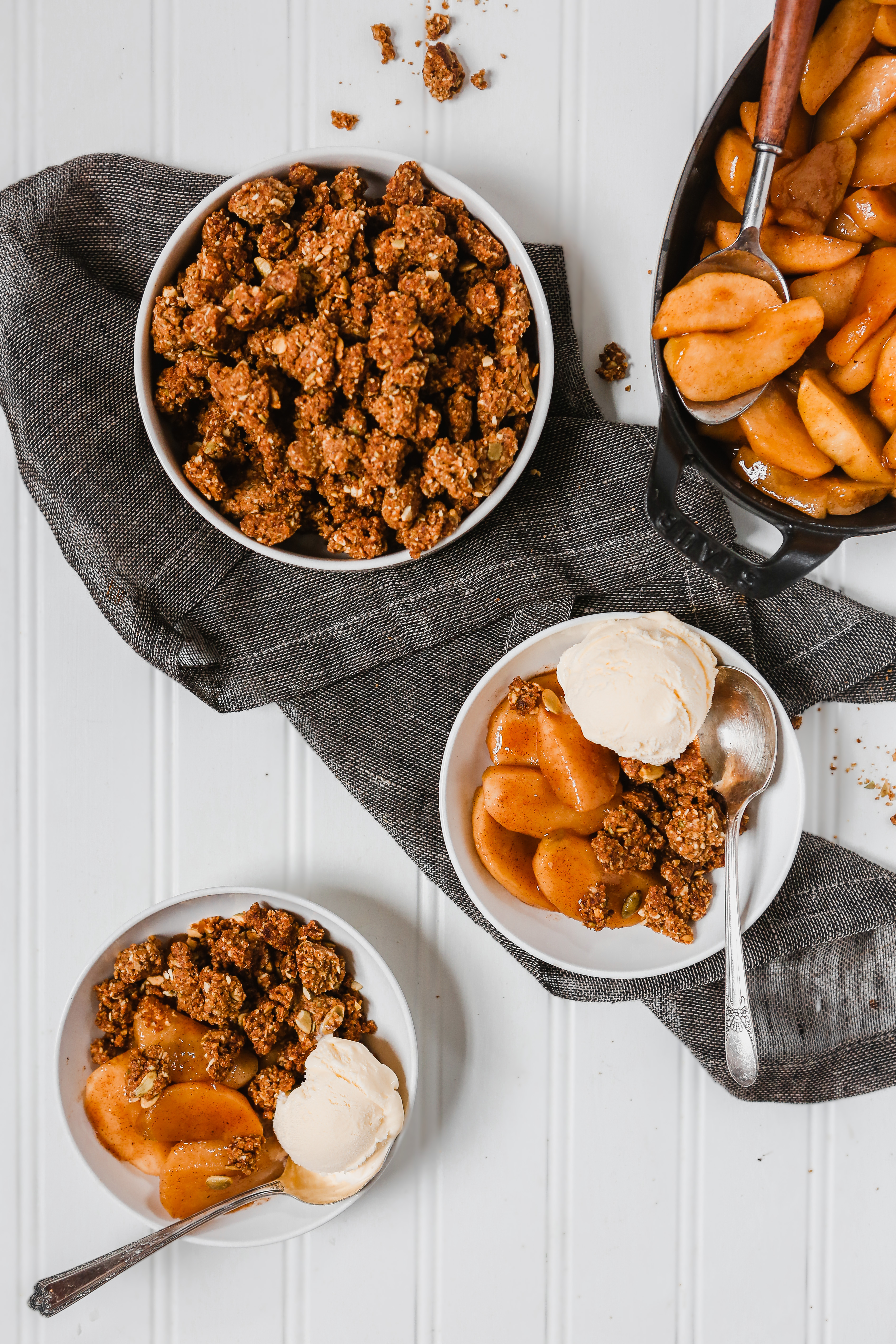 Photograph of healthy apple crisp in a white bowl set on a white background