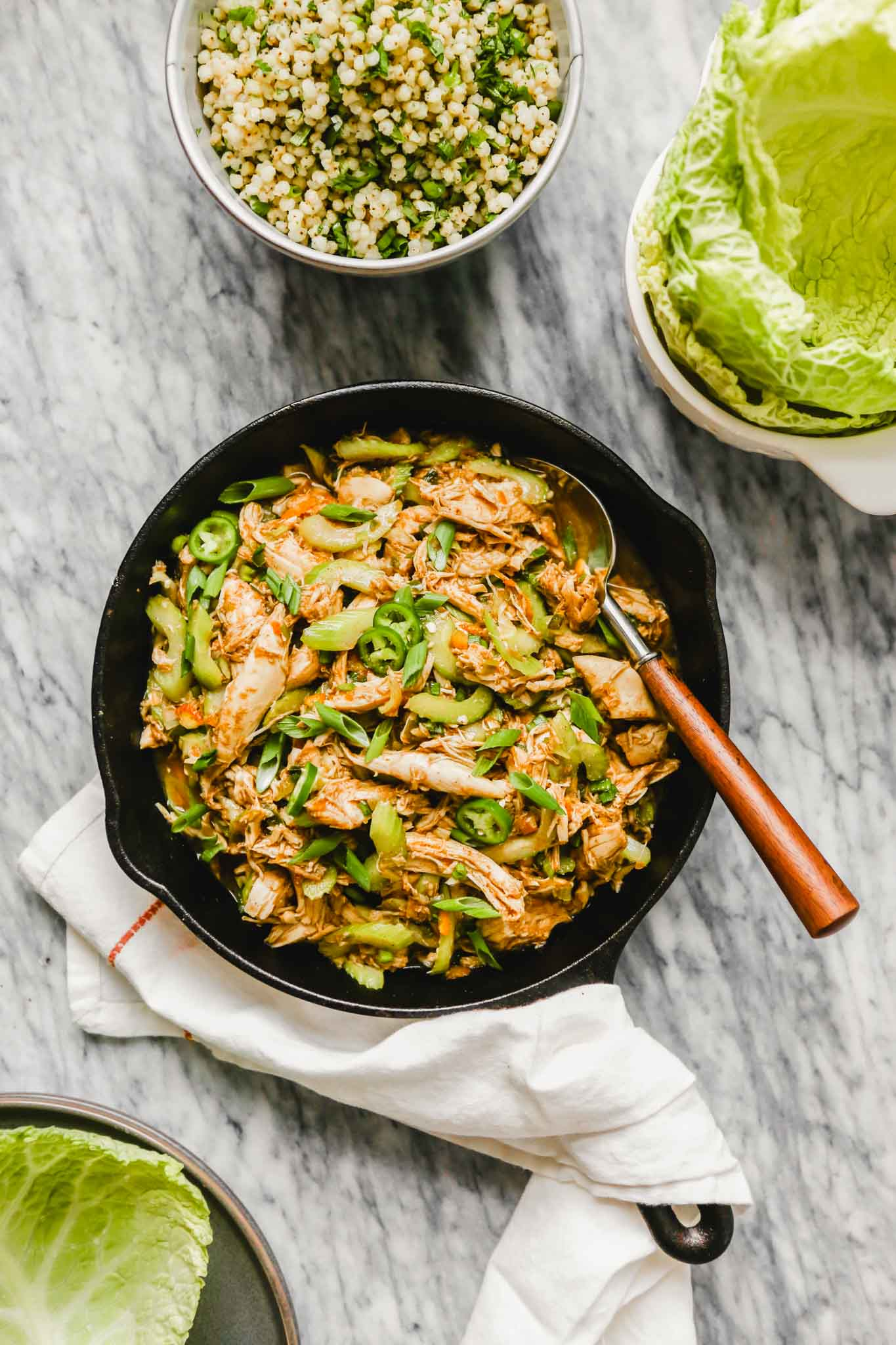 Overhead image of turkey lettuce wrap mixture in a cast iron skillet with cabbage leaves off to the side