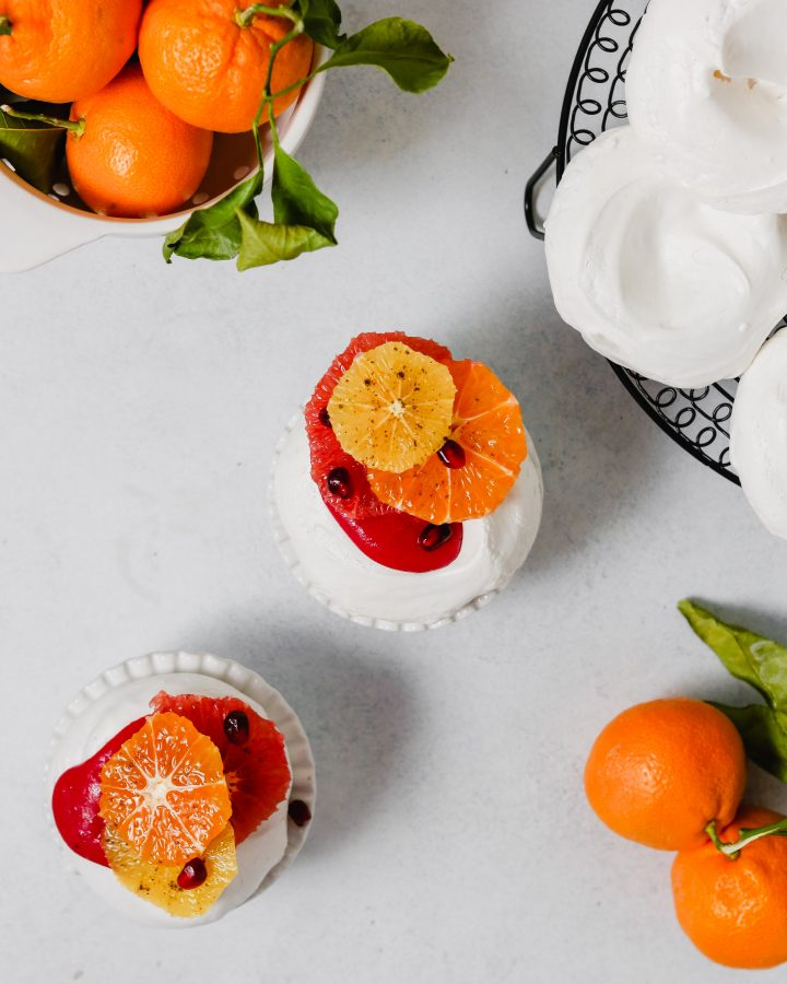 Photography of mini pavlova topped with pink cranberry curd, citrus fruit and spices.