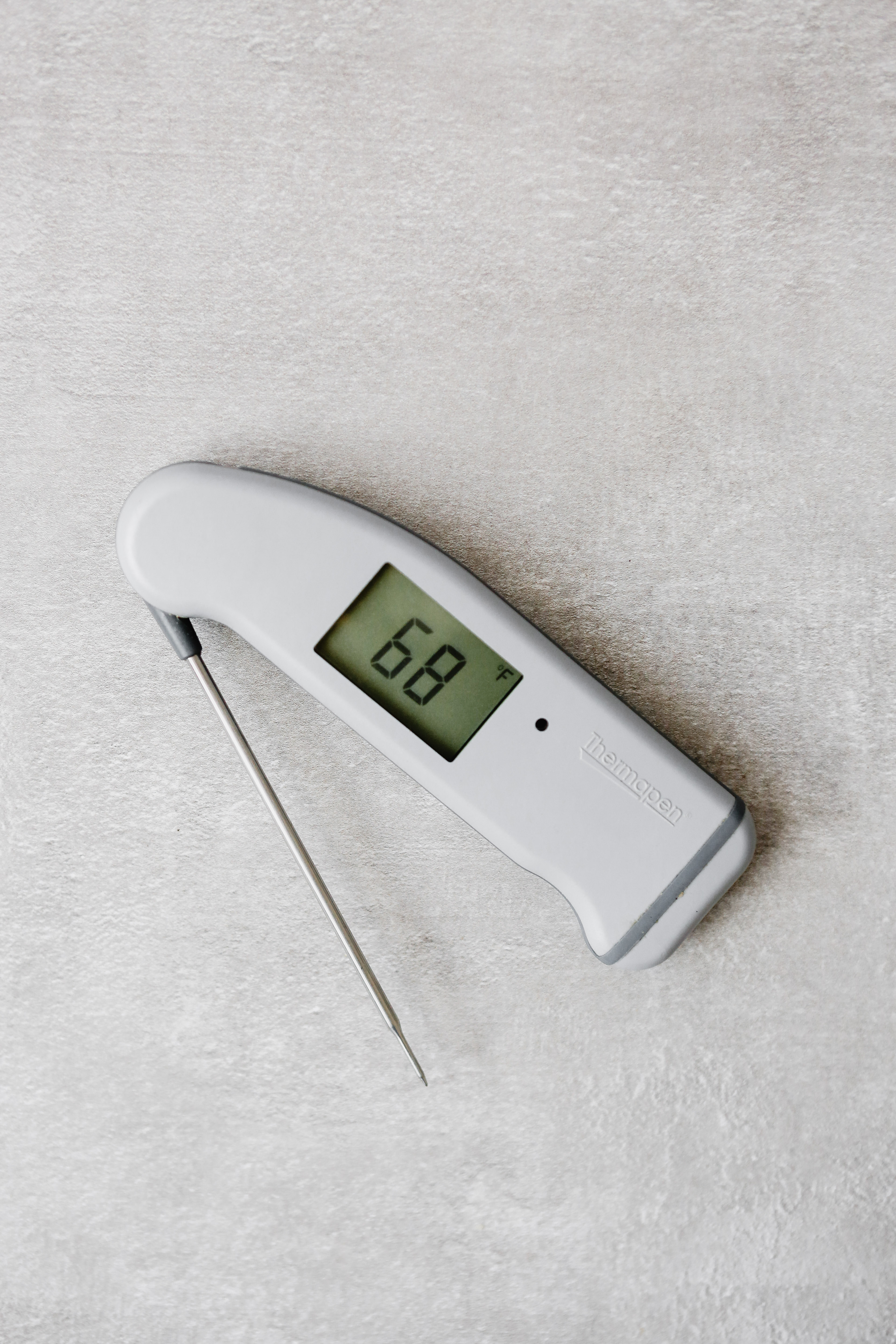 Photograph of a Thermapen thermometer on a gray table