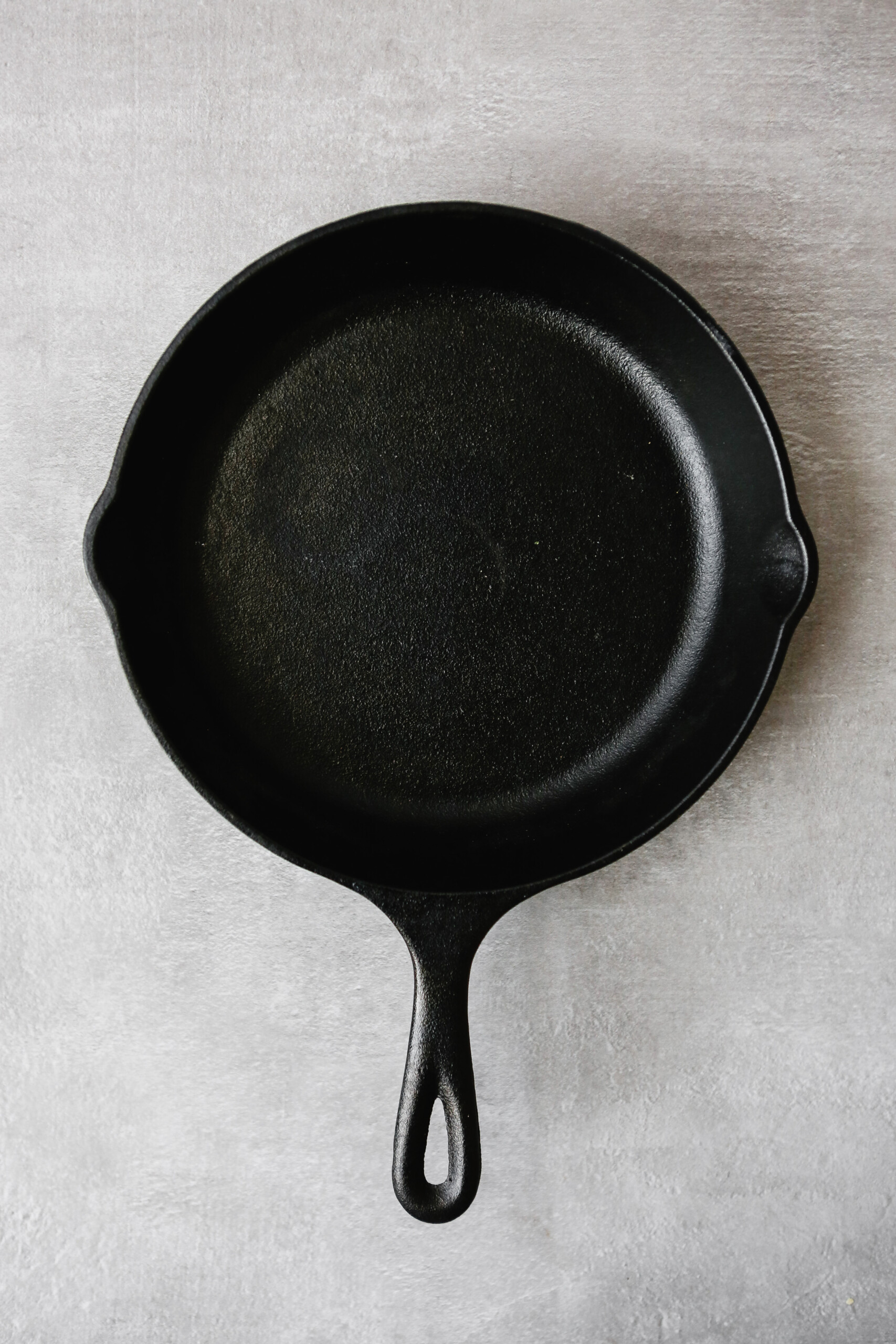 Photograph of a cast-iron skillet on a gray table