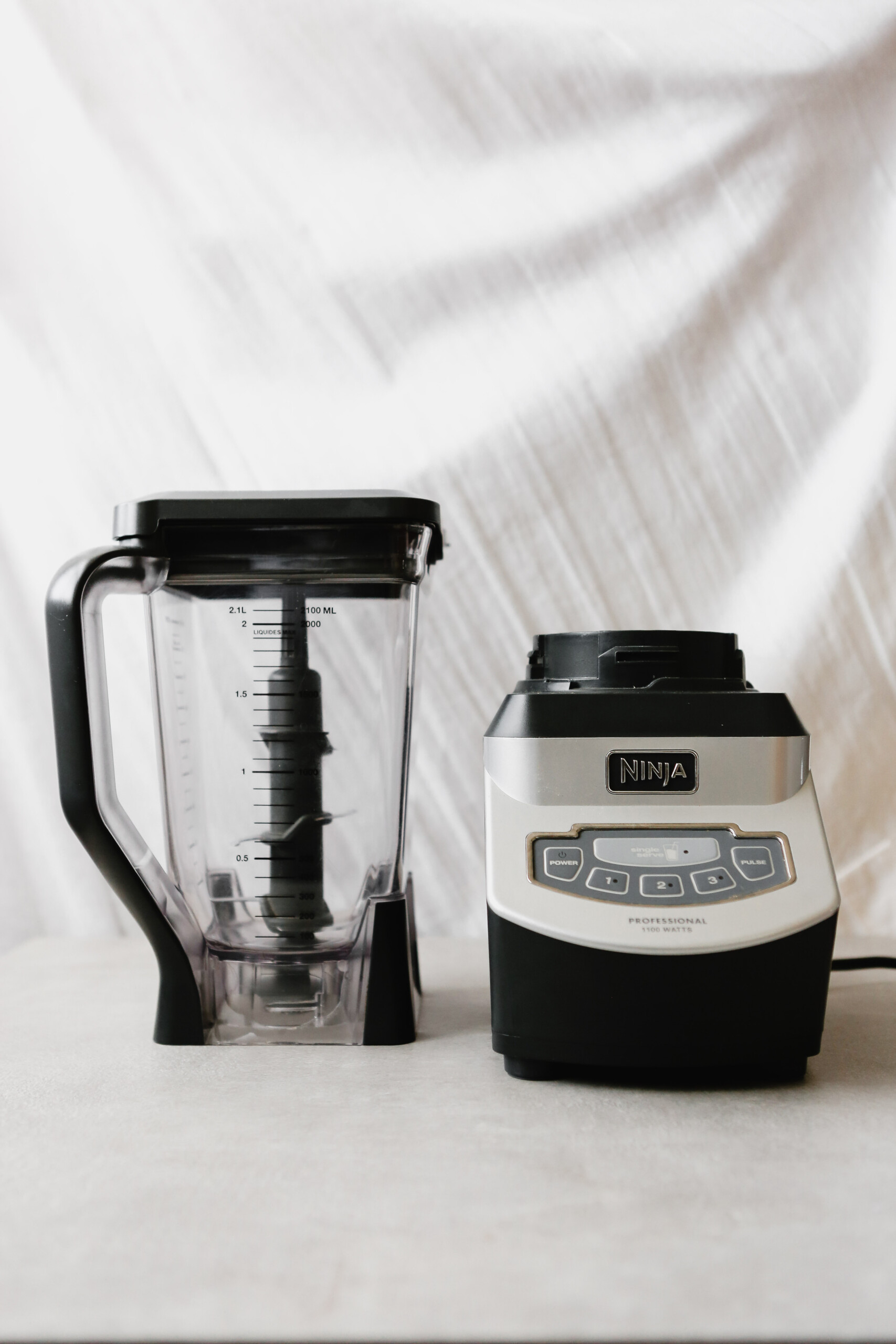 Photograph of a high-powered blender (Ninja) on a gray table with white background