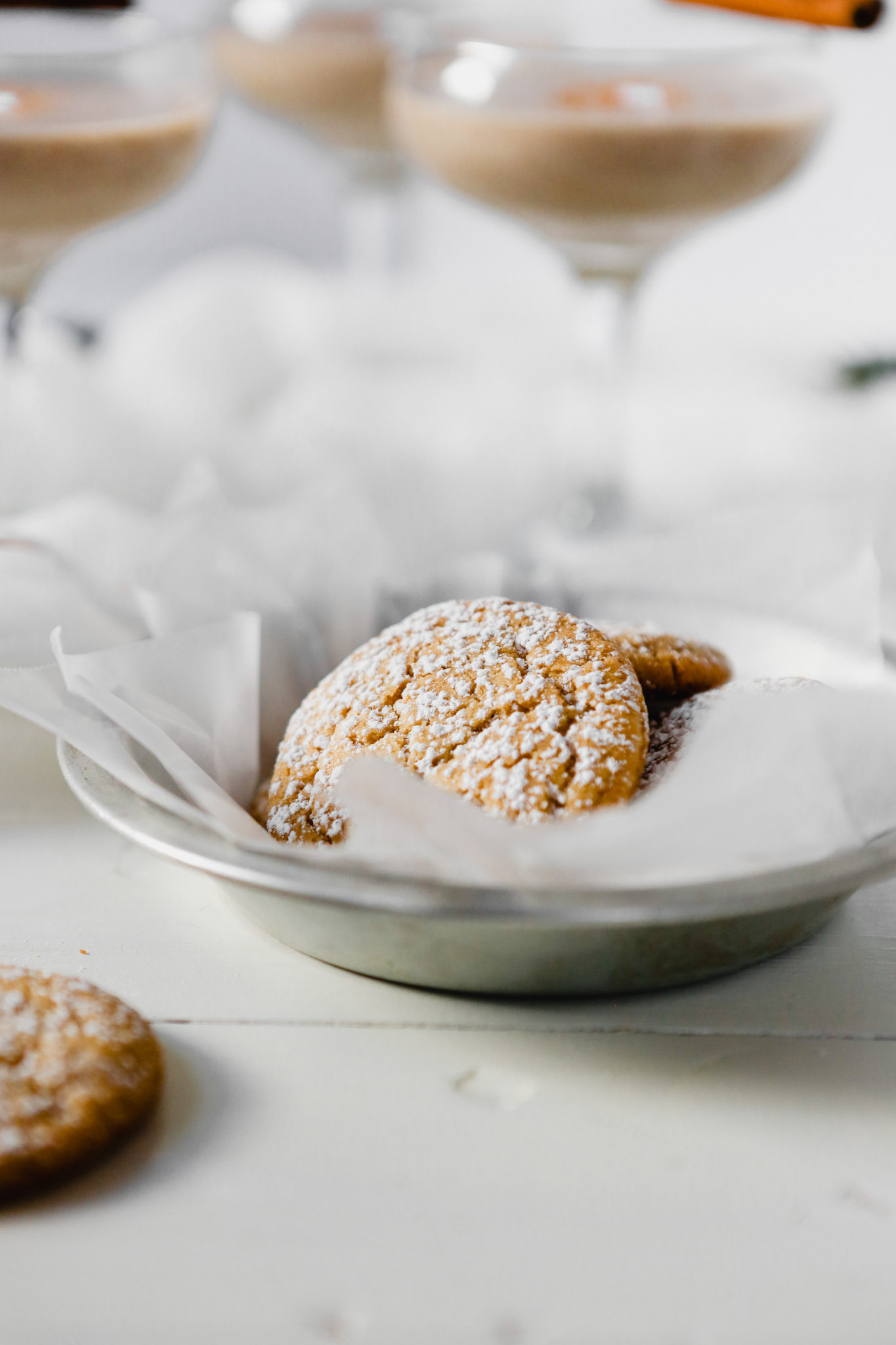 Photograph of eggnog cookies in a silver tray with glasses of eggnog set around.