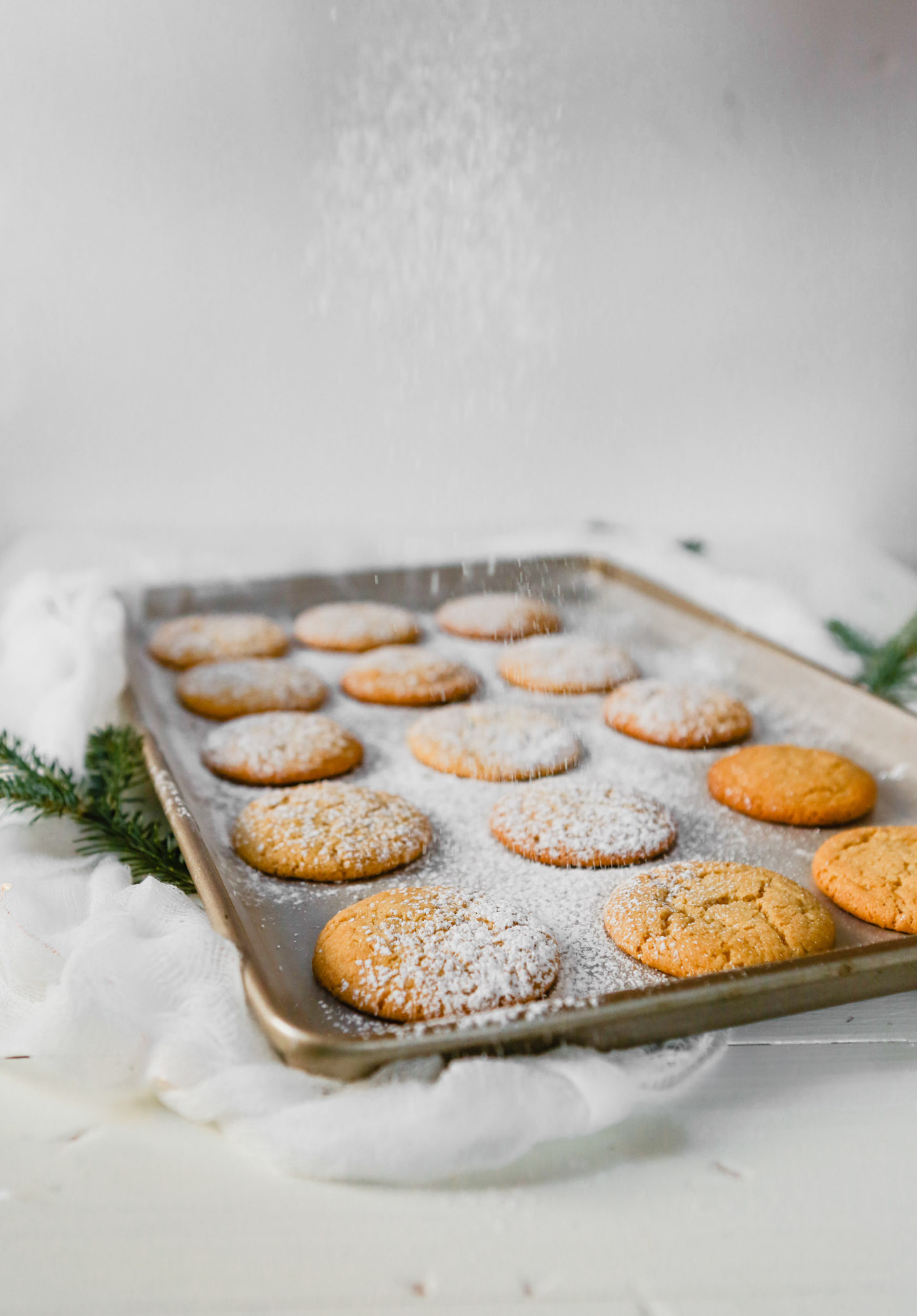 Photograph of eggnog cookies on a baking sheet getting dusted with powdered sugar
