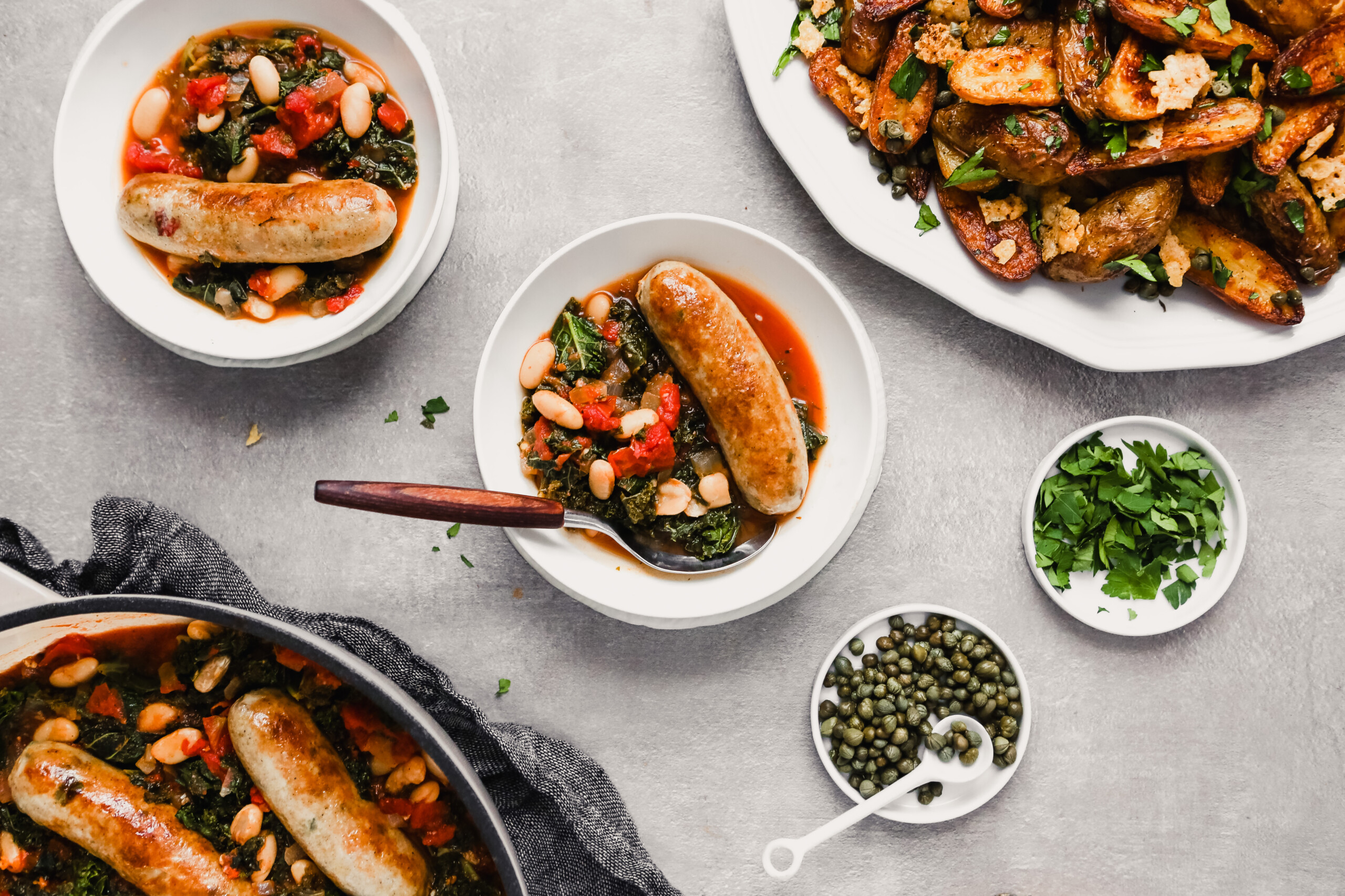Overhead photograph of bowls filled with kale, tomatoes, beans and chicken sausage