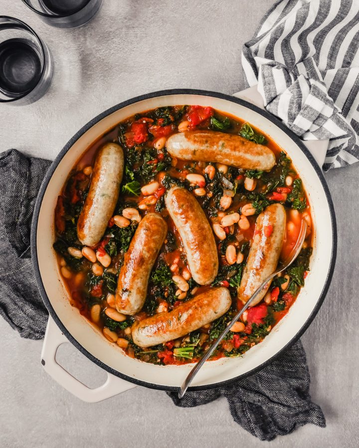Overhead photograph of a Dutch oven filled with Italian chicken sausages stewed in tomatoes, kale and white beans