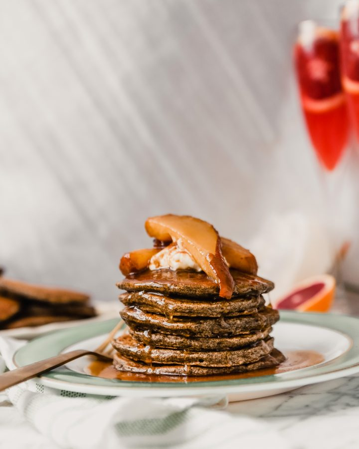 Photograph of a stack of pancakes with maple syrup dripping down them.