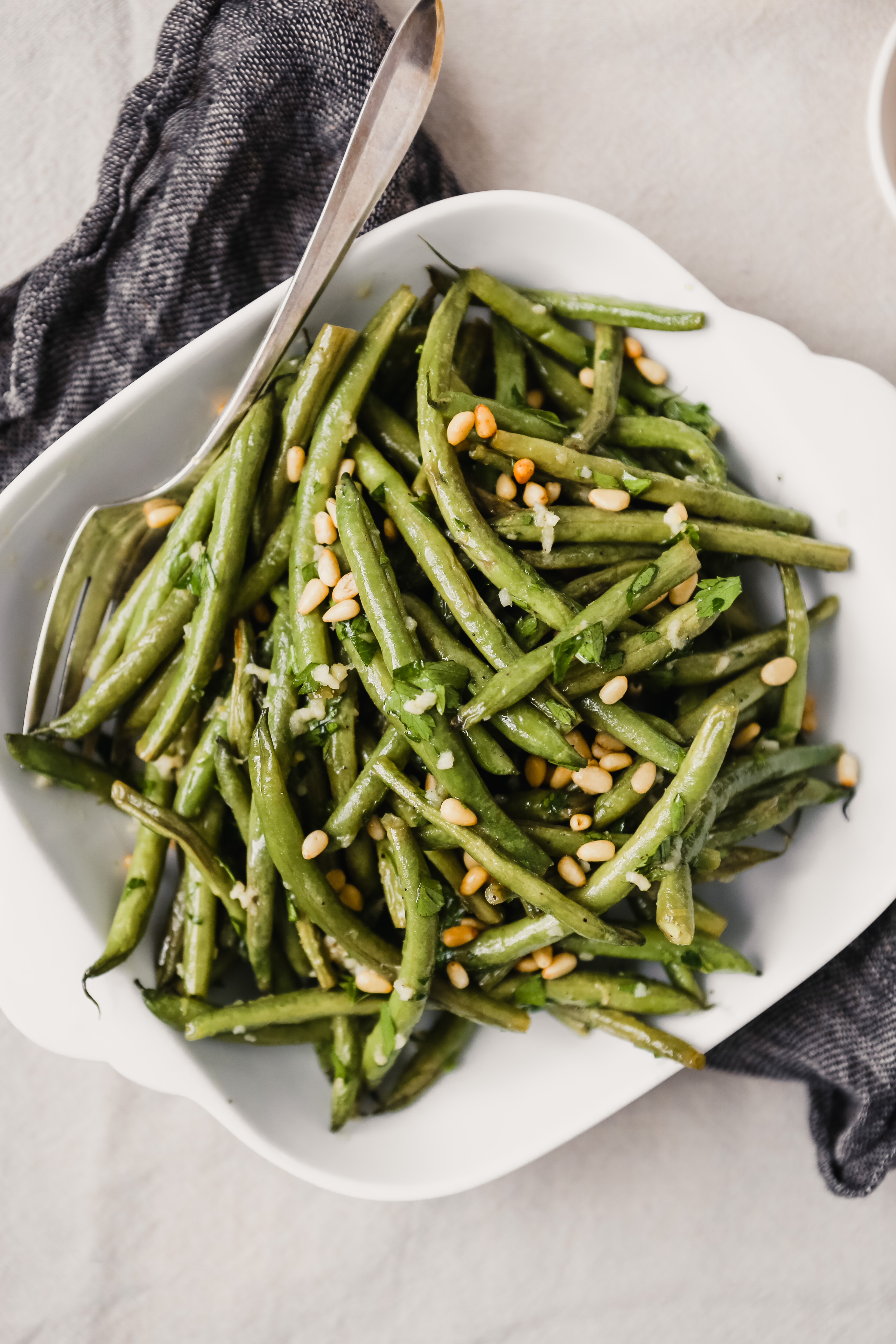 Roasted green beans with pine nuts in a square white serving dish.