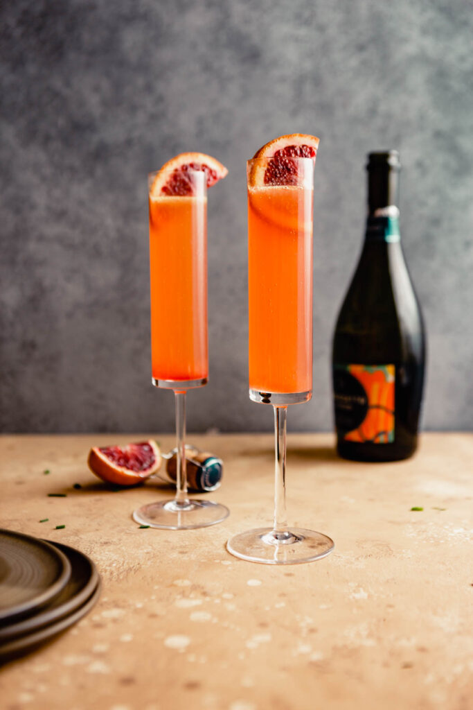 bright orange cocktail in two champagne flutes set on a brown table with a bottle of sparkling wine in the background