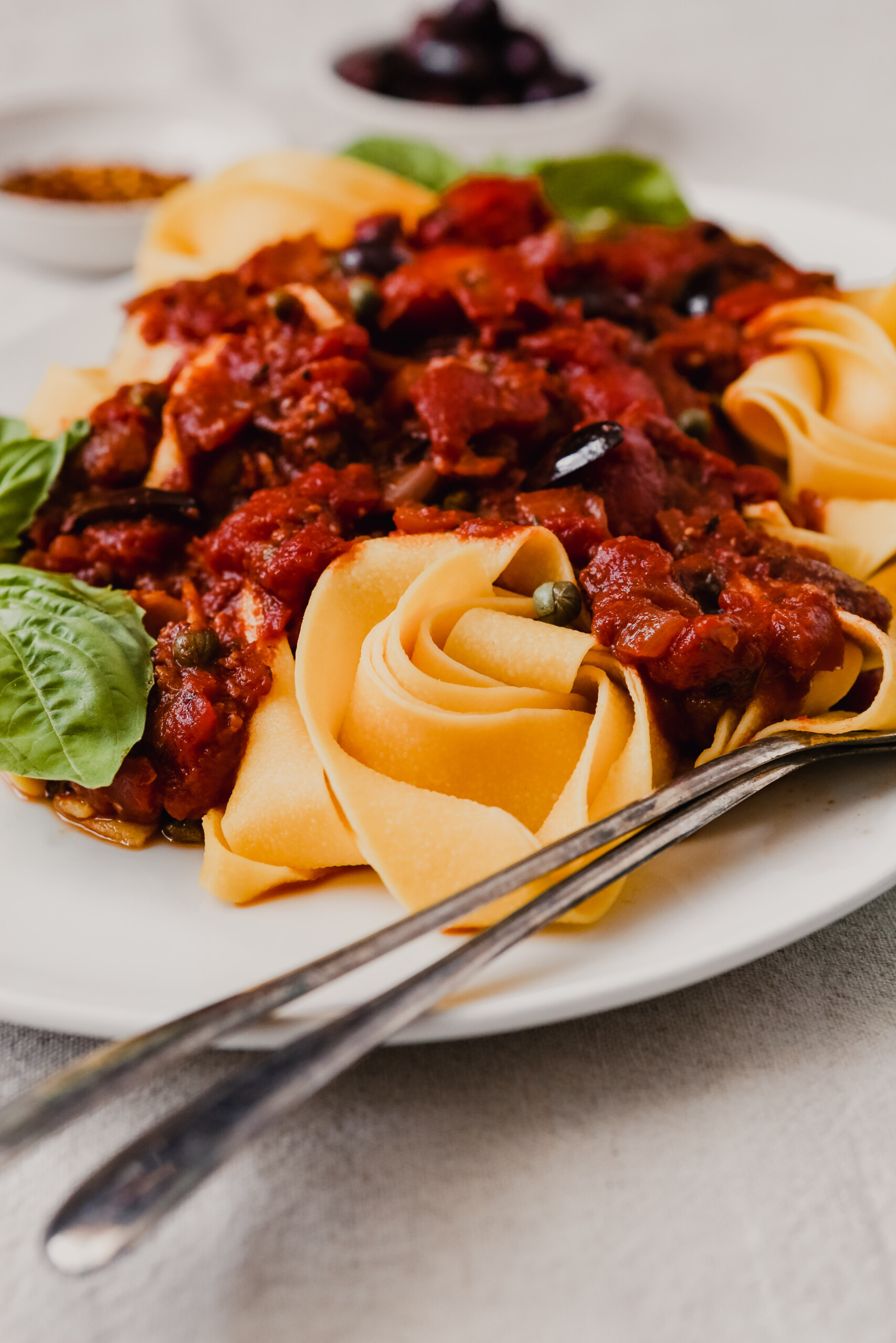 Close up photograph of pappardelle pasta topped with puttanesca sauce.