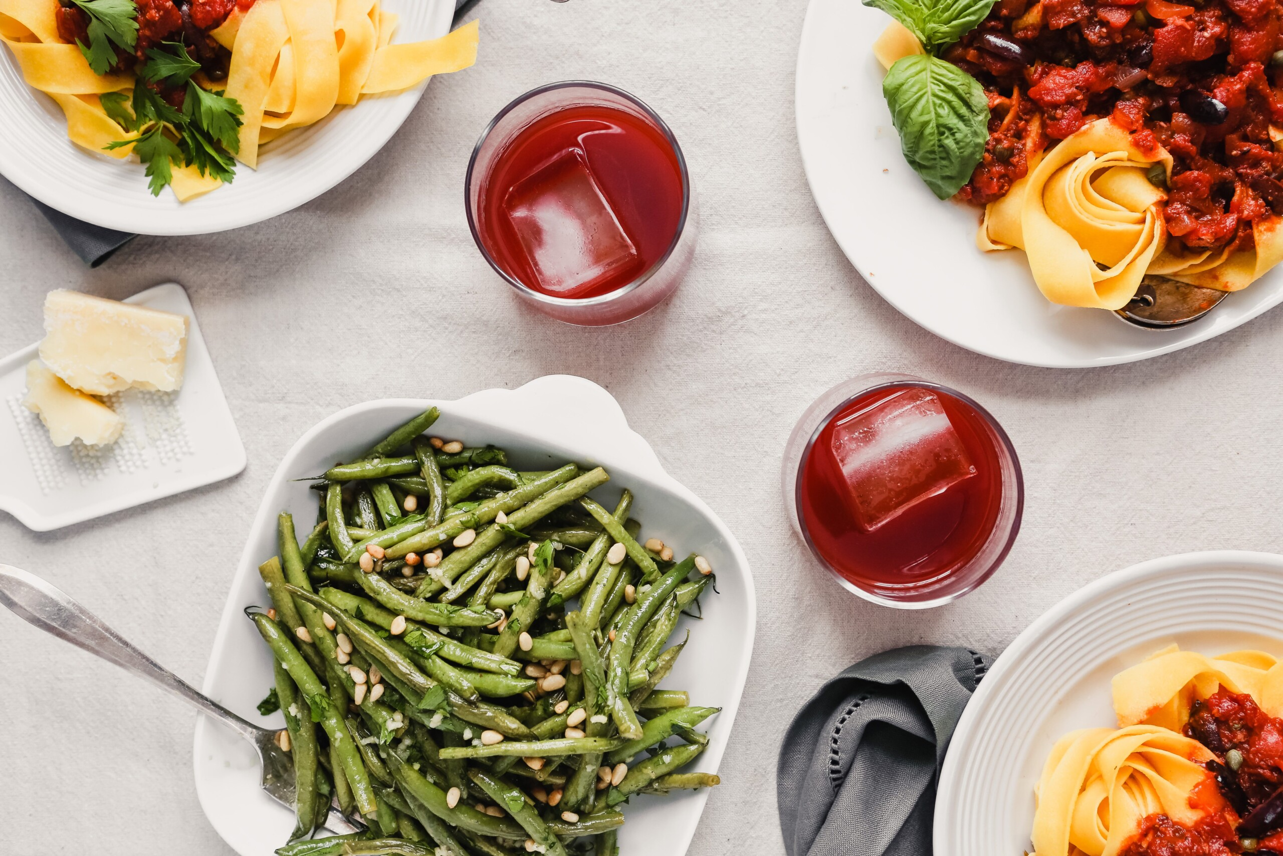 Photograph of an Italian dinner spread, green beans in a white bowl, glasses of Negroni and plates of pasta with red sauce