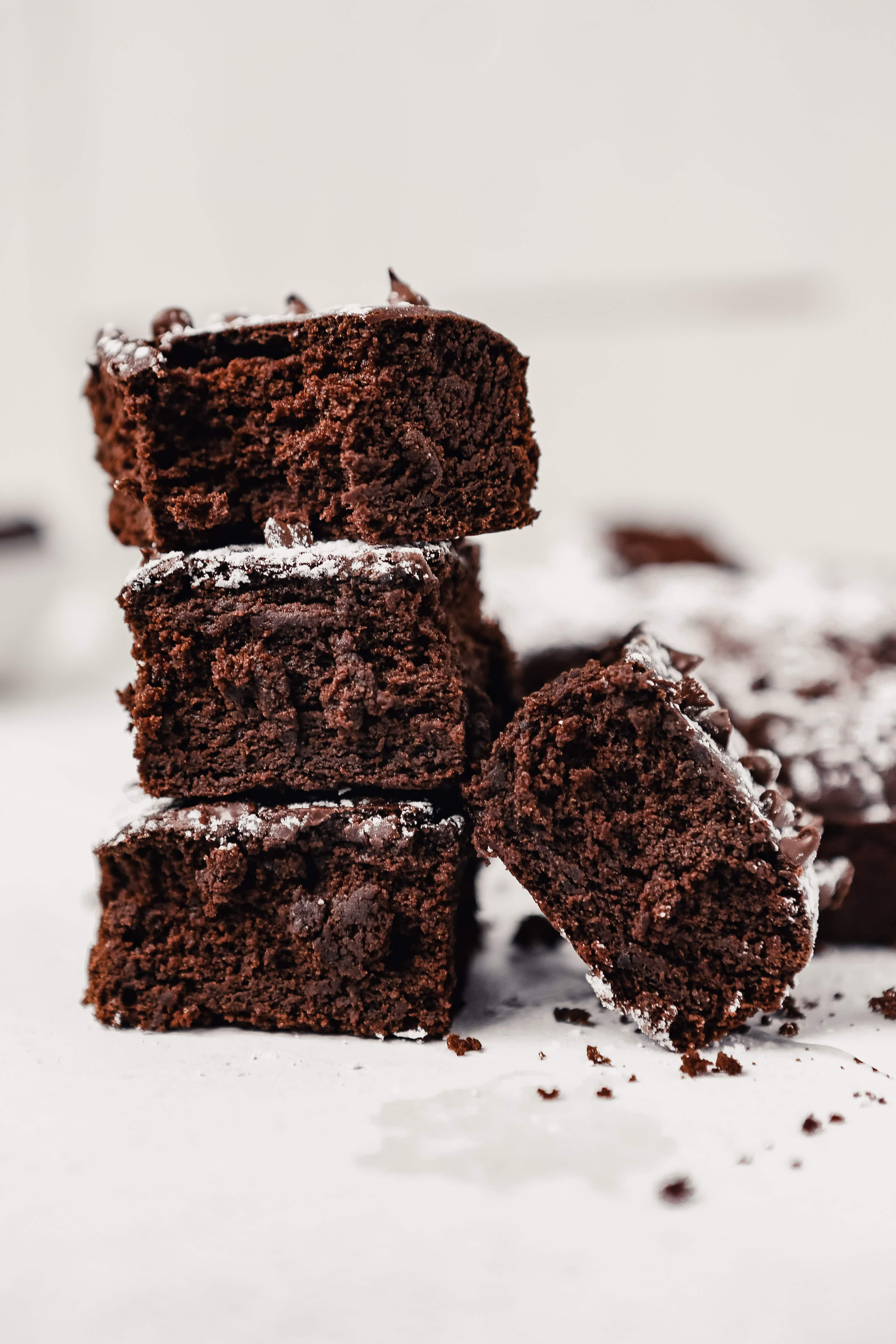 Photograph of a batch of brownies stacked on top of eachother on a white surface cut into squares and dusted with powdered sugar