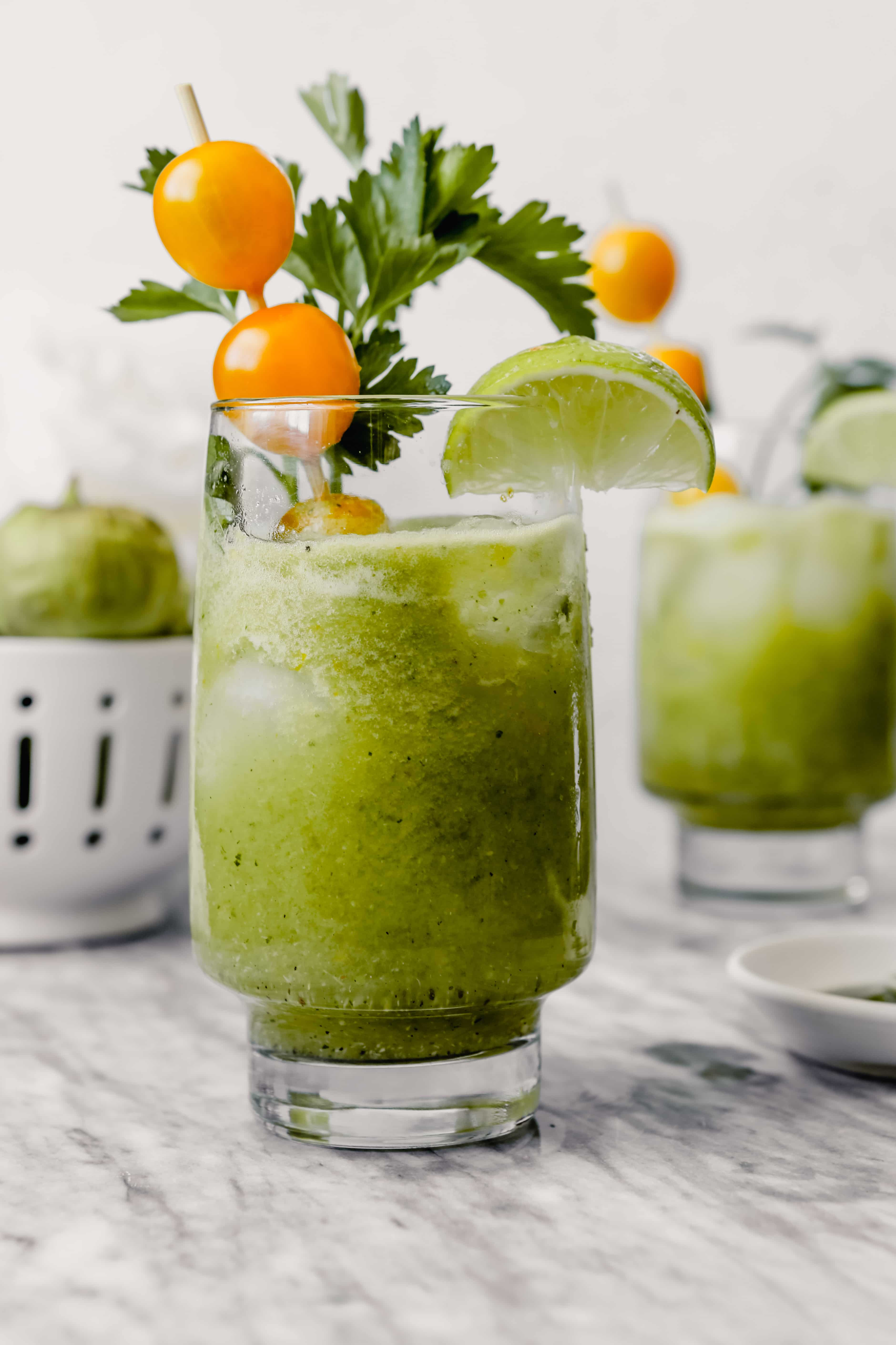 Photograph of green bloody mary in tall collins glass garnishes with yellow cherry tomatoes, herbs, lime wedge and apple slice.