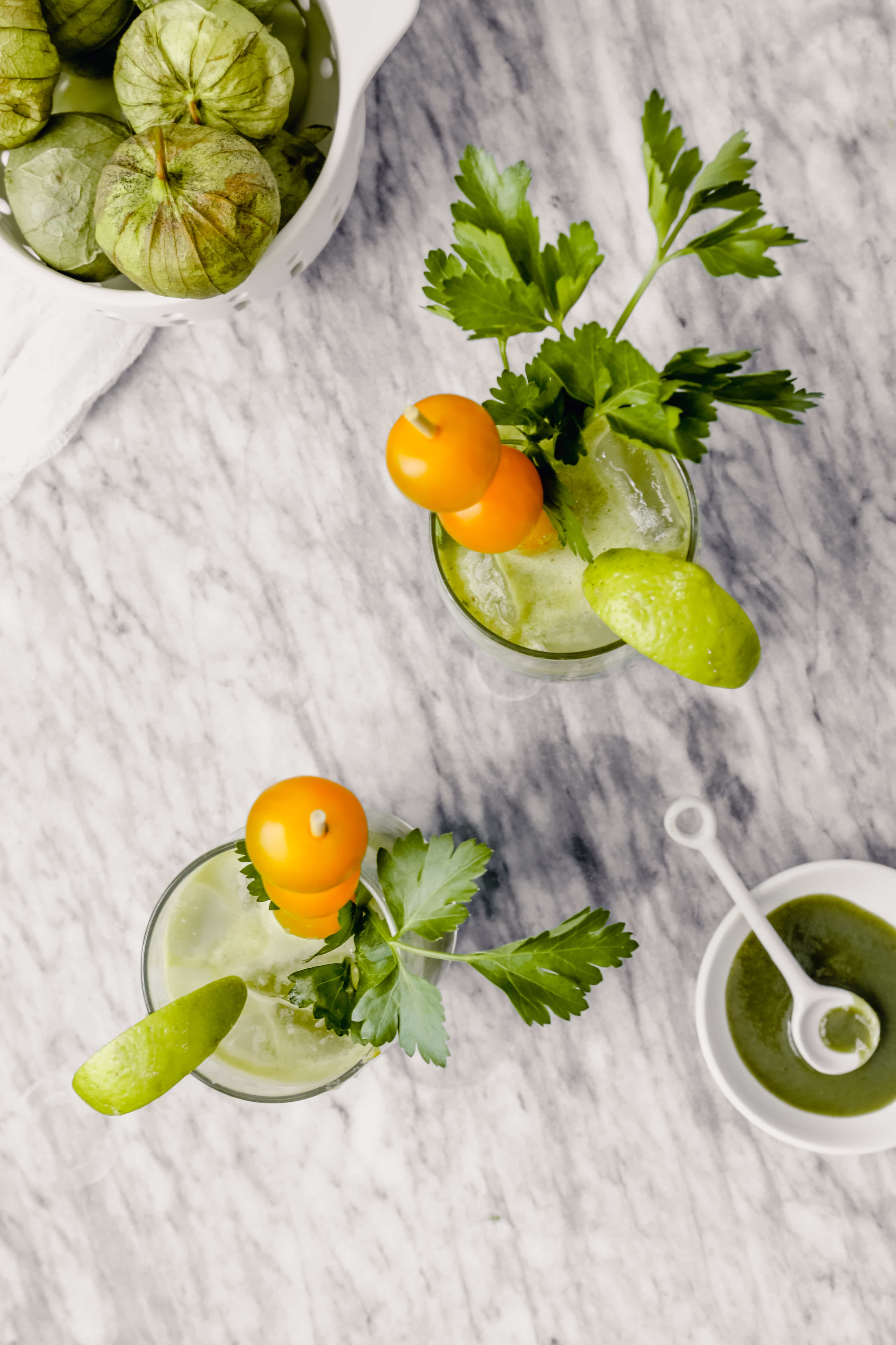 Overhead photograph of green bloody mary in tall collins glass garnishes with yellow cherry tomatoes, herbs, lime wedge and apple slice.