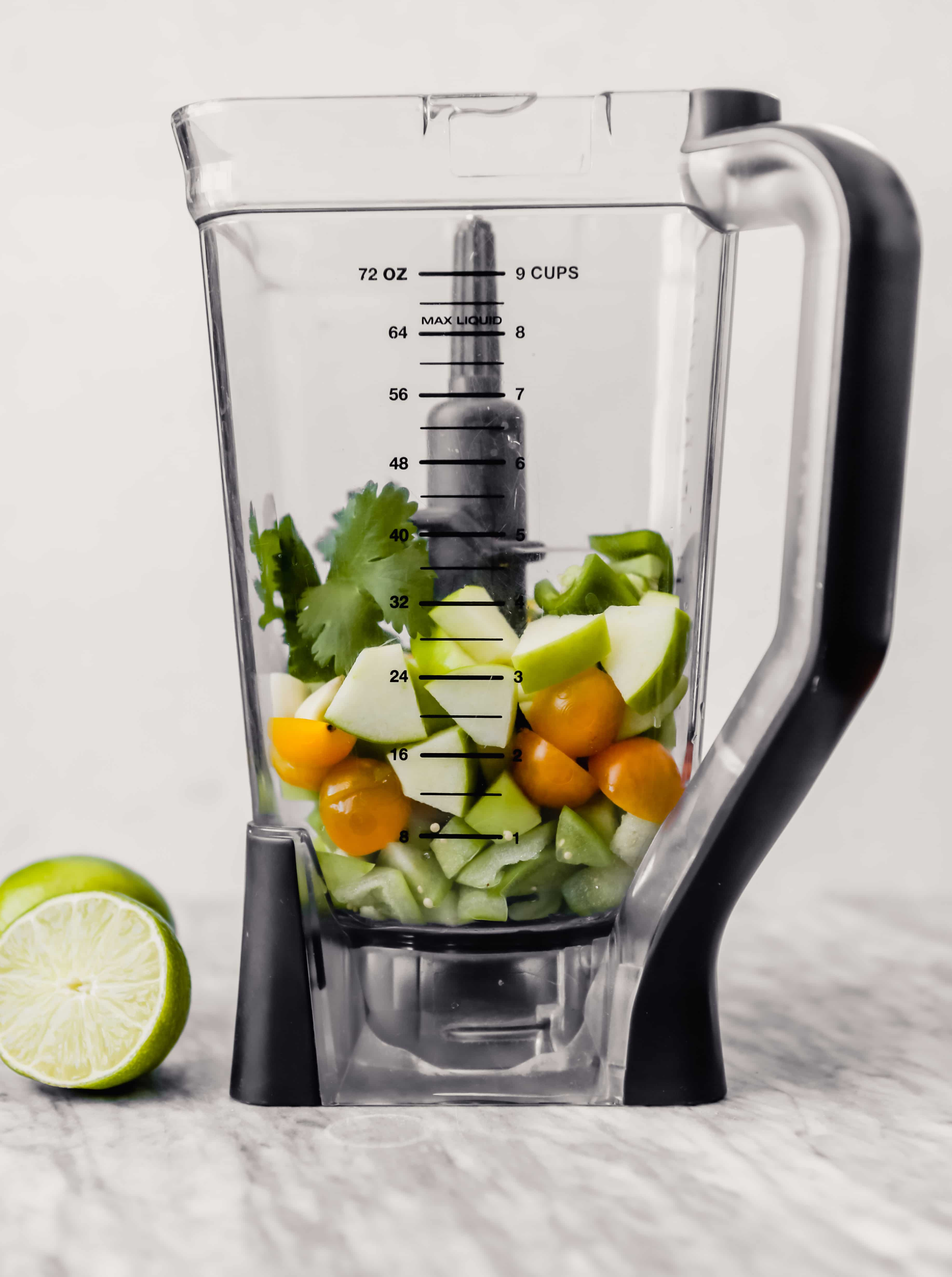 Tomatillos, cherry tomatoes, apple, and herbs in a blender