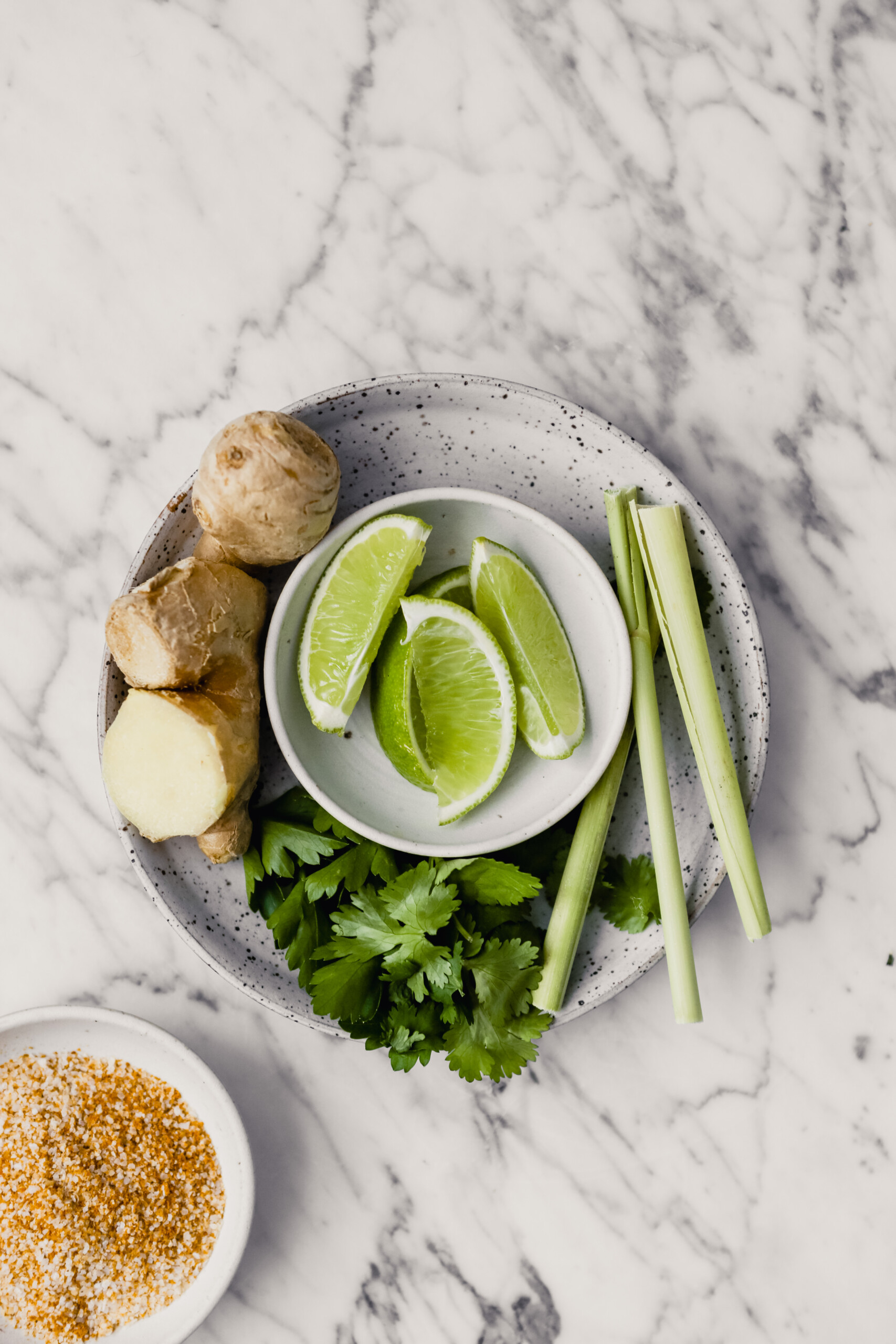 Photograph of ginger, lime wedges, lemongrass and fresh herbs arranged on a white speckled plate