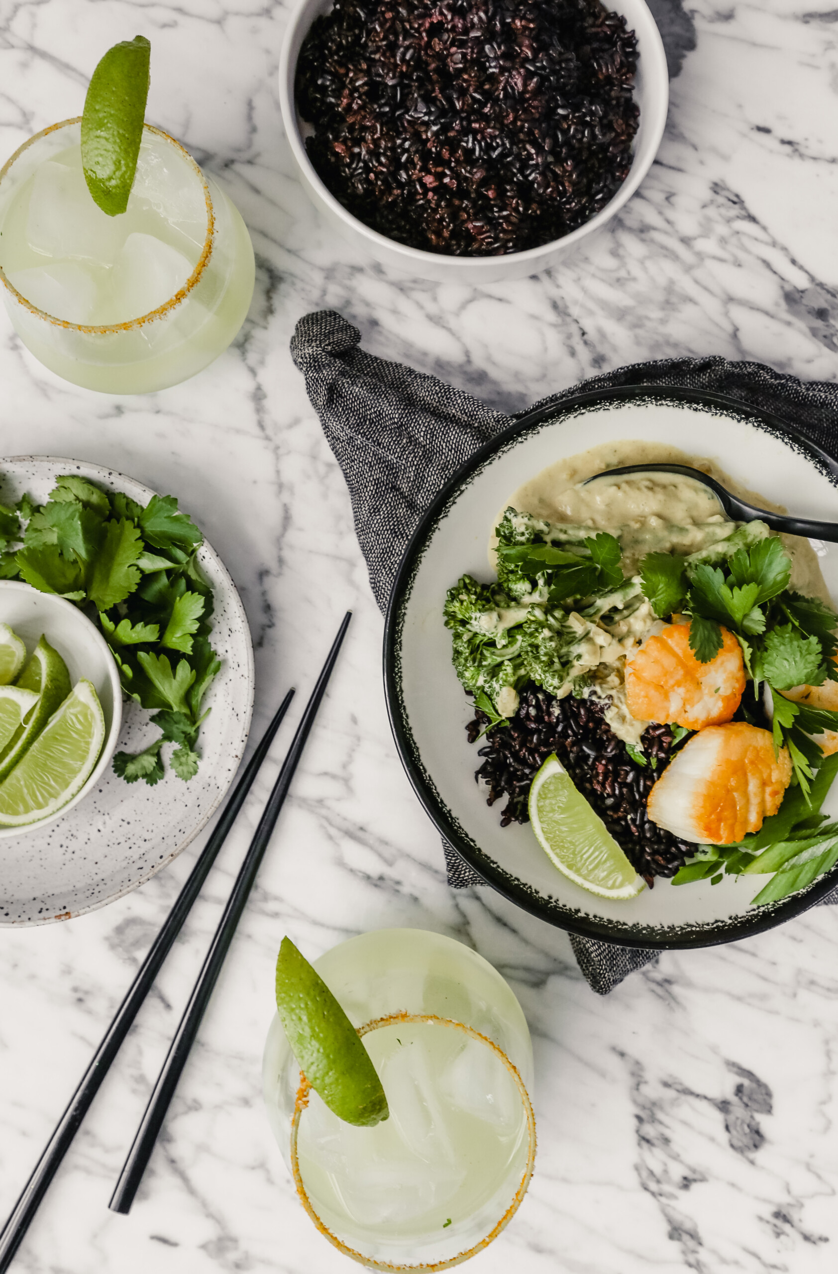 Photograph of a bowl filled with green coconut curry, black rice, broccolini and golden scallops set on a marble table with a gray napkin and margaritas set around.