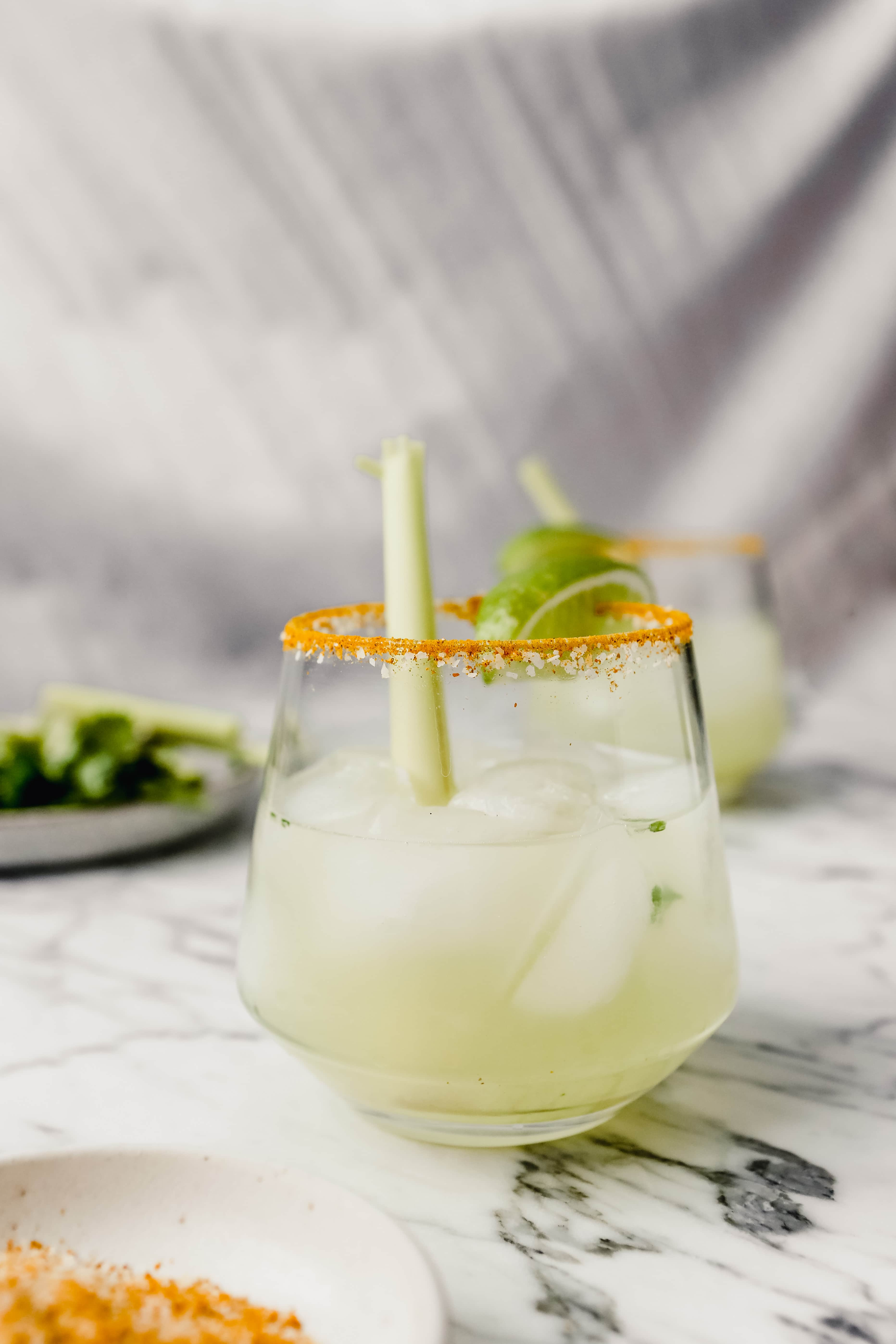 Photograph of a margarita set on a white marble table garnished with a lime wedge and lemongrass.