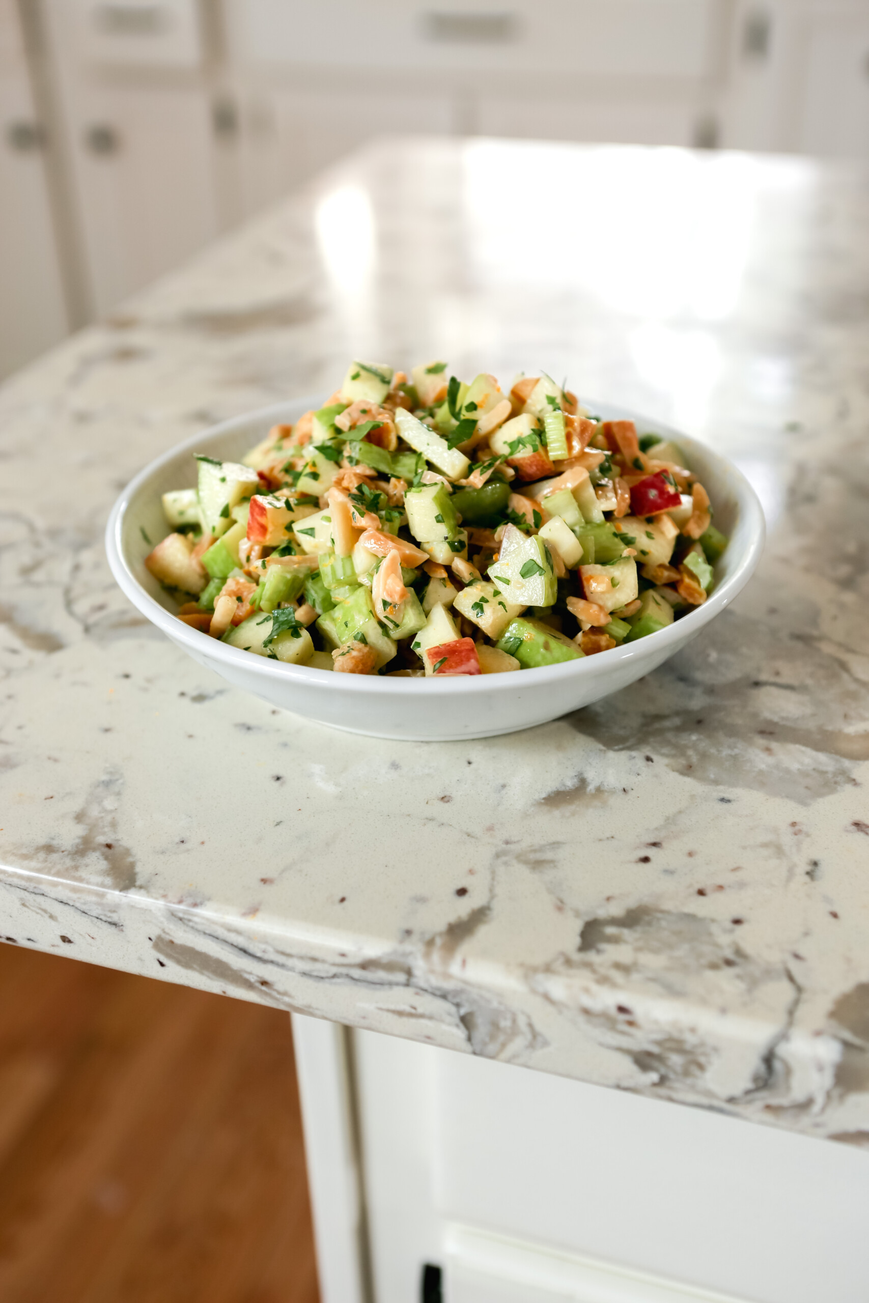 Photograph of diced apple salad in a white bowl on a cream-colored marble table.