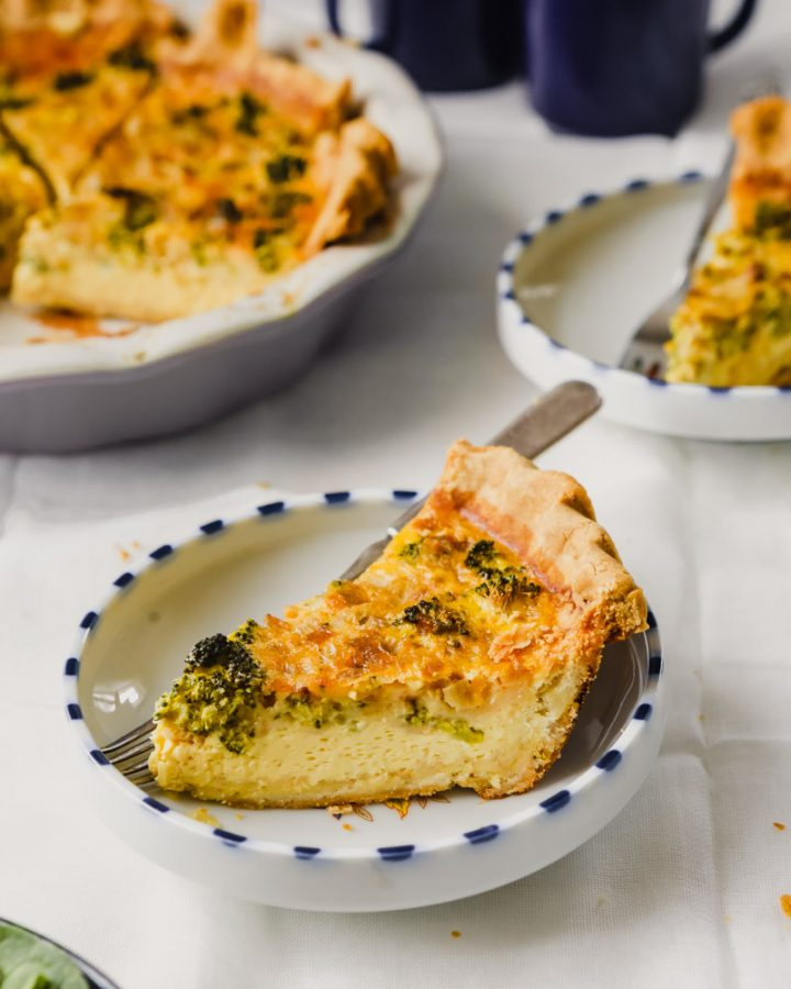Photograph of a slice of quiche set in a white and blue spotted bowl on a marble table.
