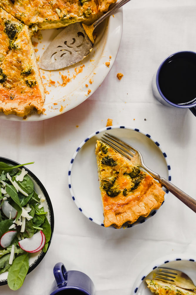 Photograph of a piece of quiche set in a small white plate with salad and coffee set around