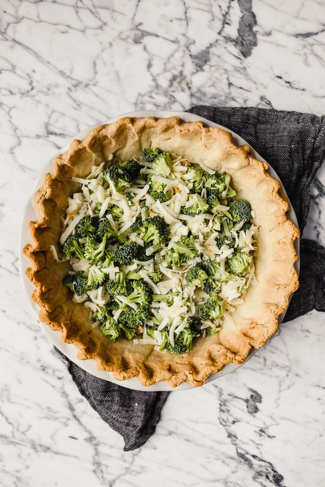 Photograph of cheese and broccoli sprinkled in the base of a baked pie shell