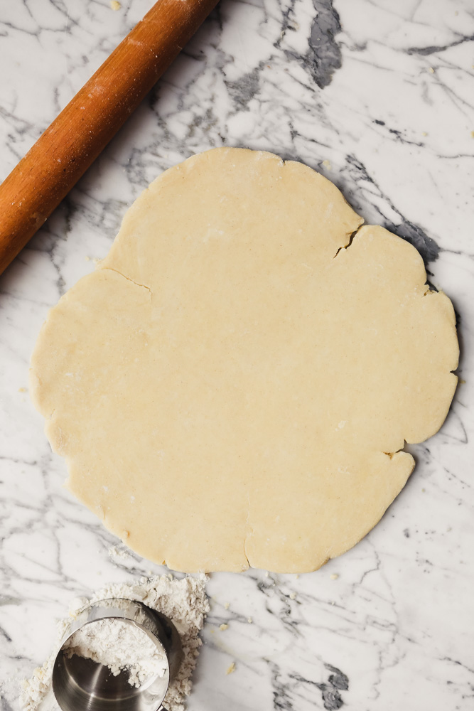 Photograph of gluten-free pie dough rolled out into a circle on a white marble surface