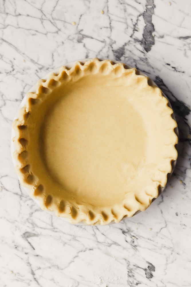Photograph of a pie plate lined with pie dough set on a white marble table
