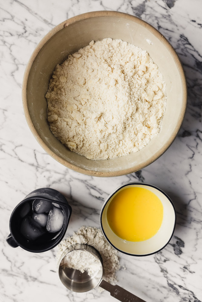 Photograph of a large bowl filled with gluten-free flour with 3 small bowls around it filled with a beaten egg, ice water and extra flour