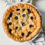 blueberry rhubarb pie set on a white table with a stripped napkin