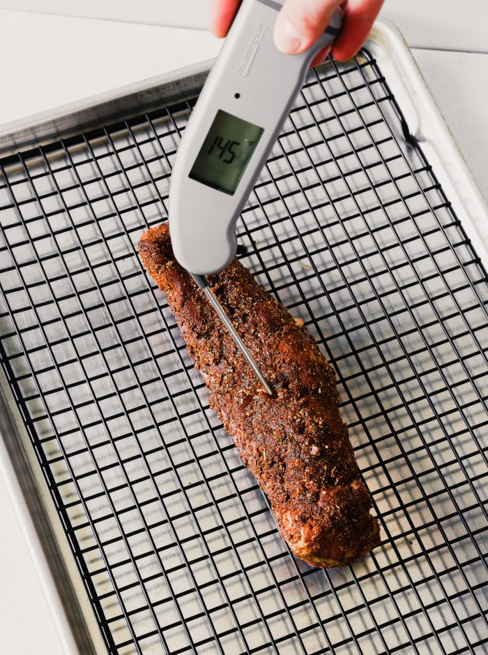 Photograph of a pork tenderloin's internal temperature being checked with an instant-read thermometer.