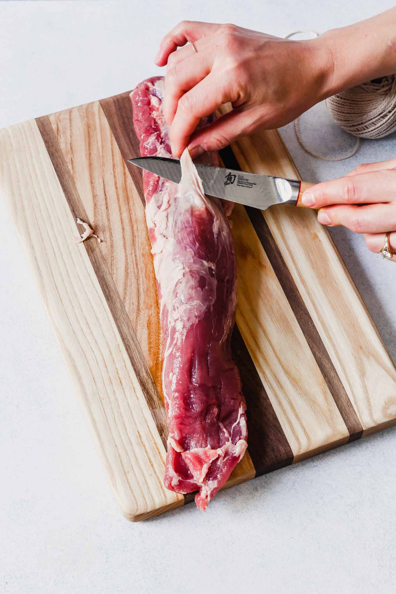 Photograph of someone trimming the silver skin from a pork tenderloin
