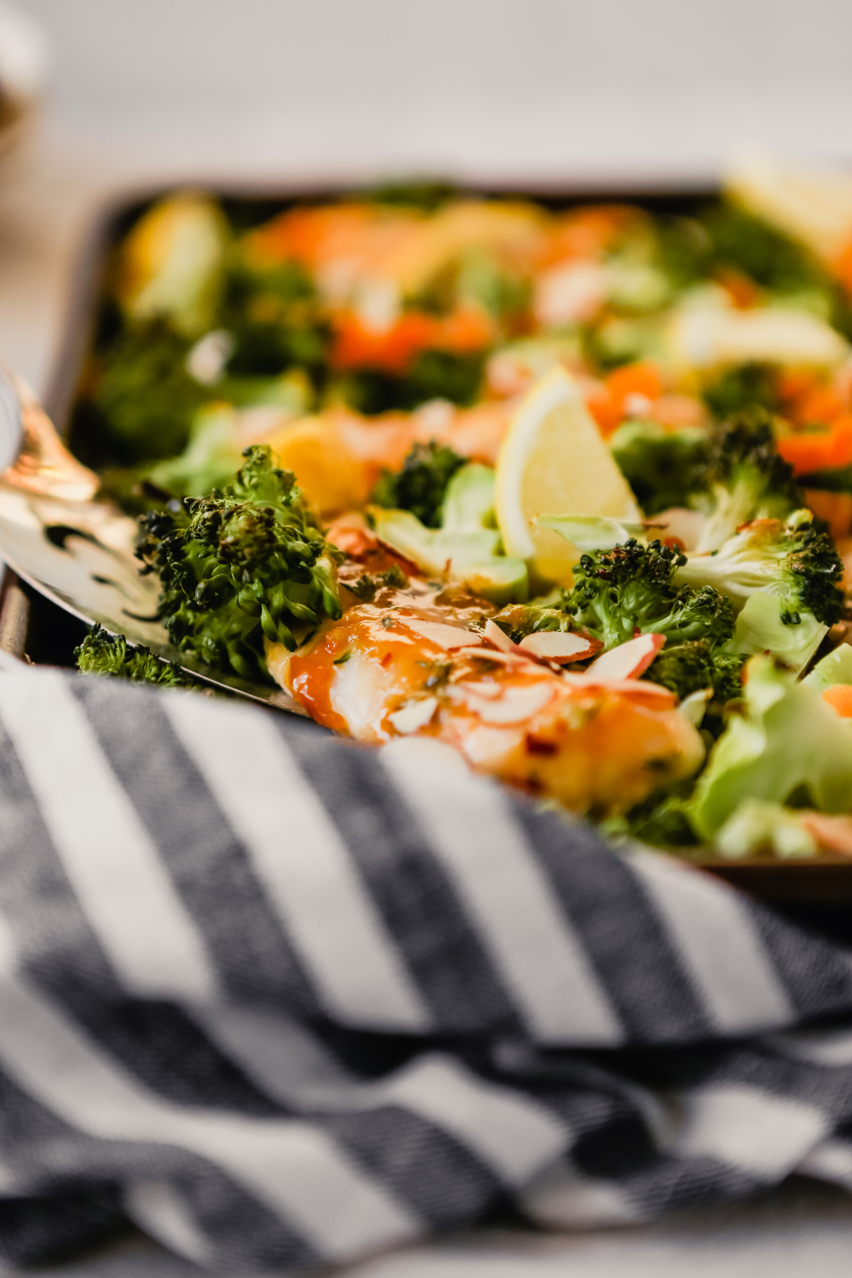 Photograph of apricot-glazed chicken on a sheet pan with broccoli, almond and lemon wedges.