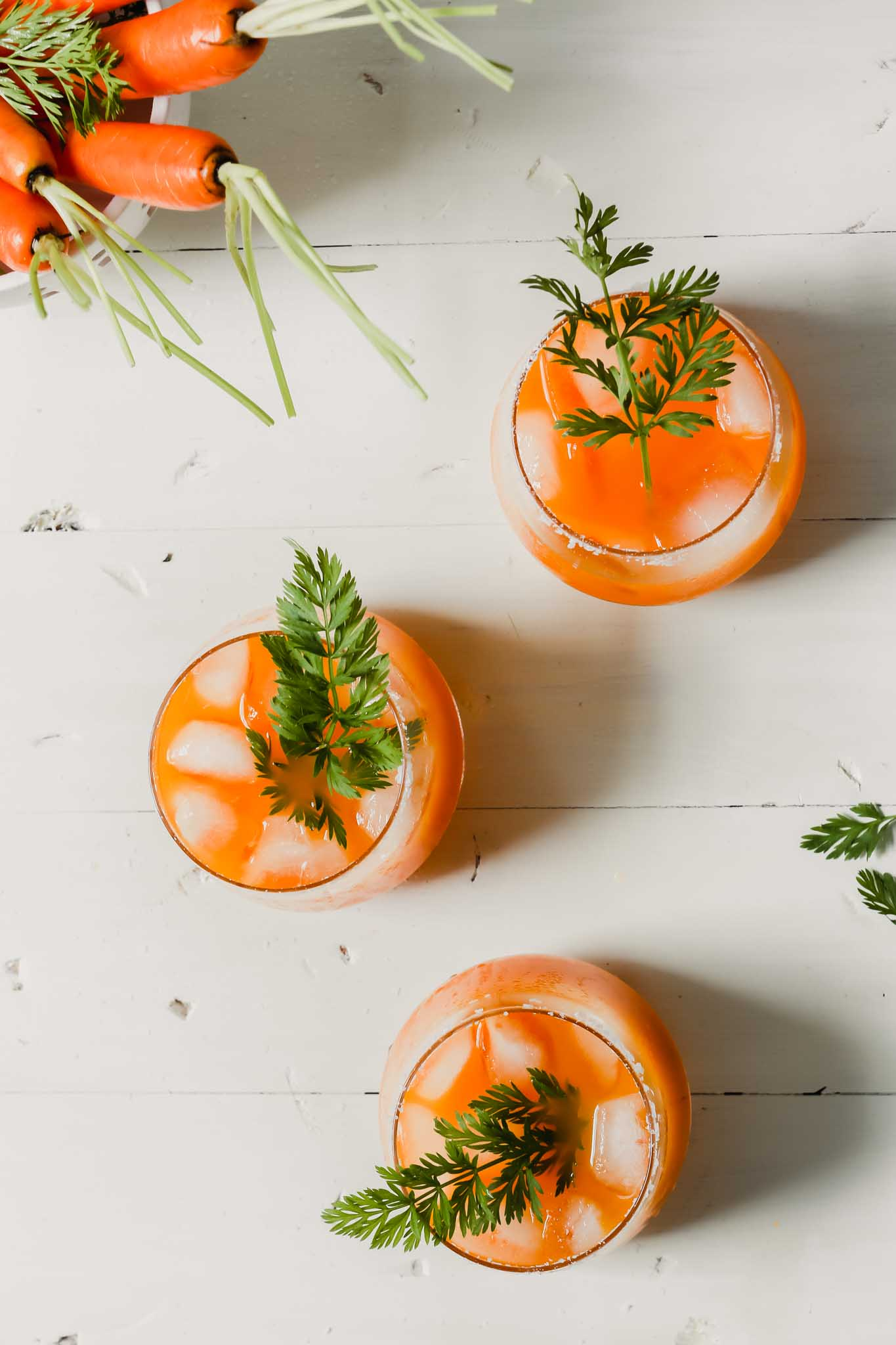 Overhead photograph of carrot cocktails with carrot tops as garnish set on a white wood table.