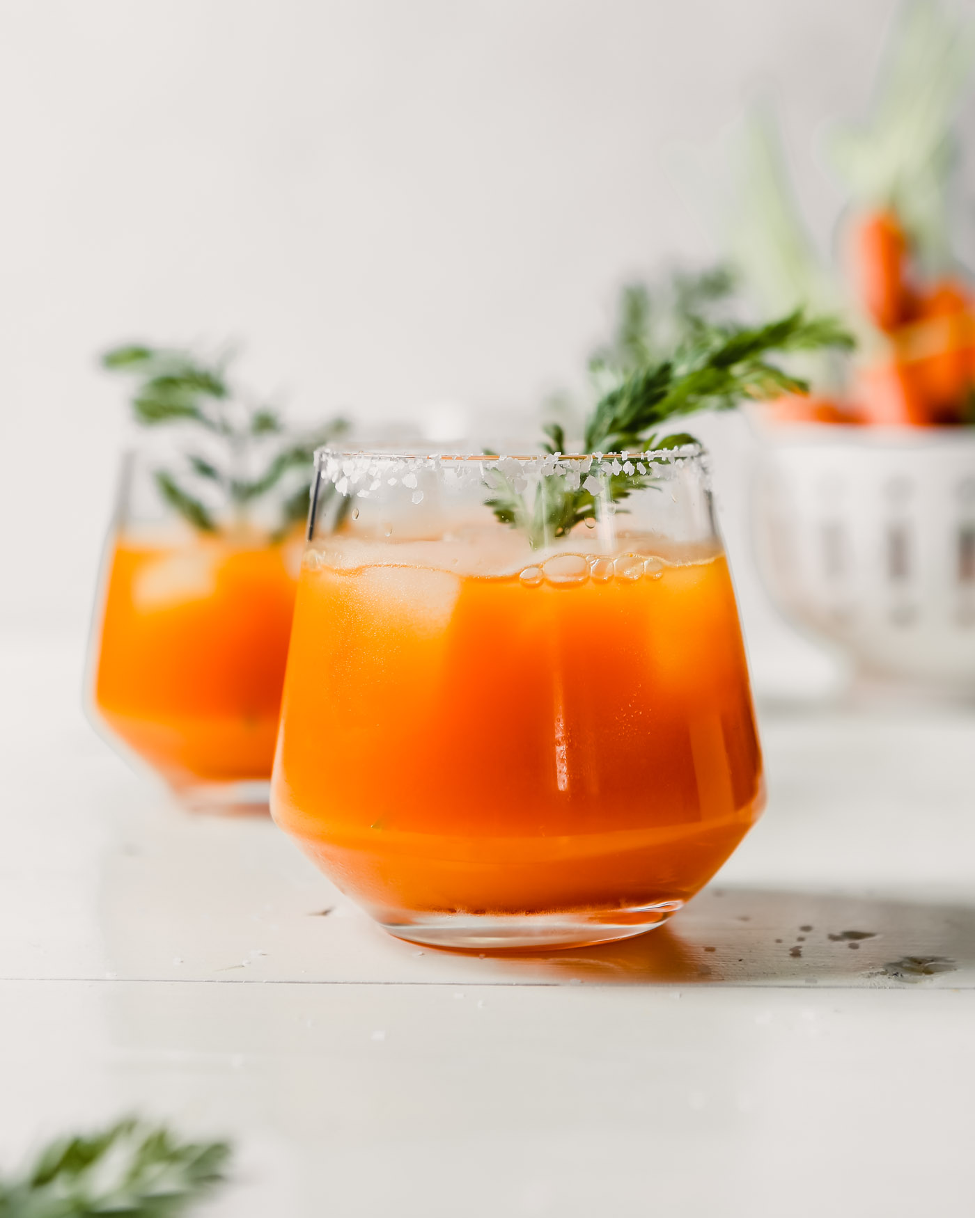 Photograph of carrot cocktails with carrot tops as garnish set on a white wood table.