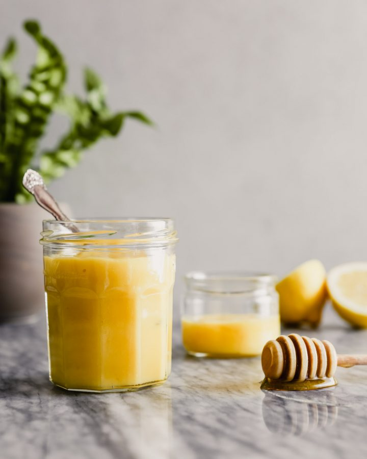 Photograph of lemon curd in a glass jar set on a marble table.