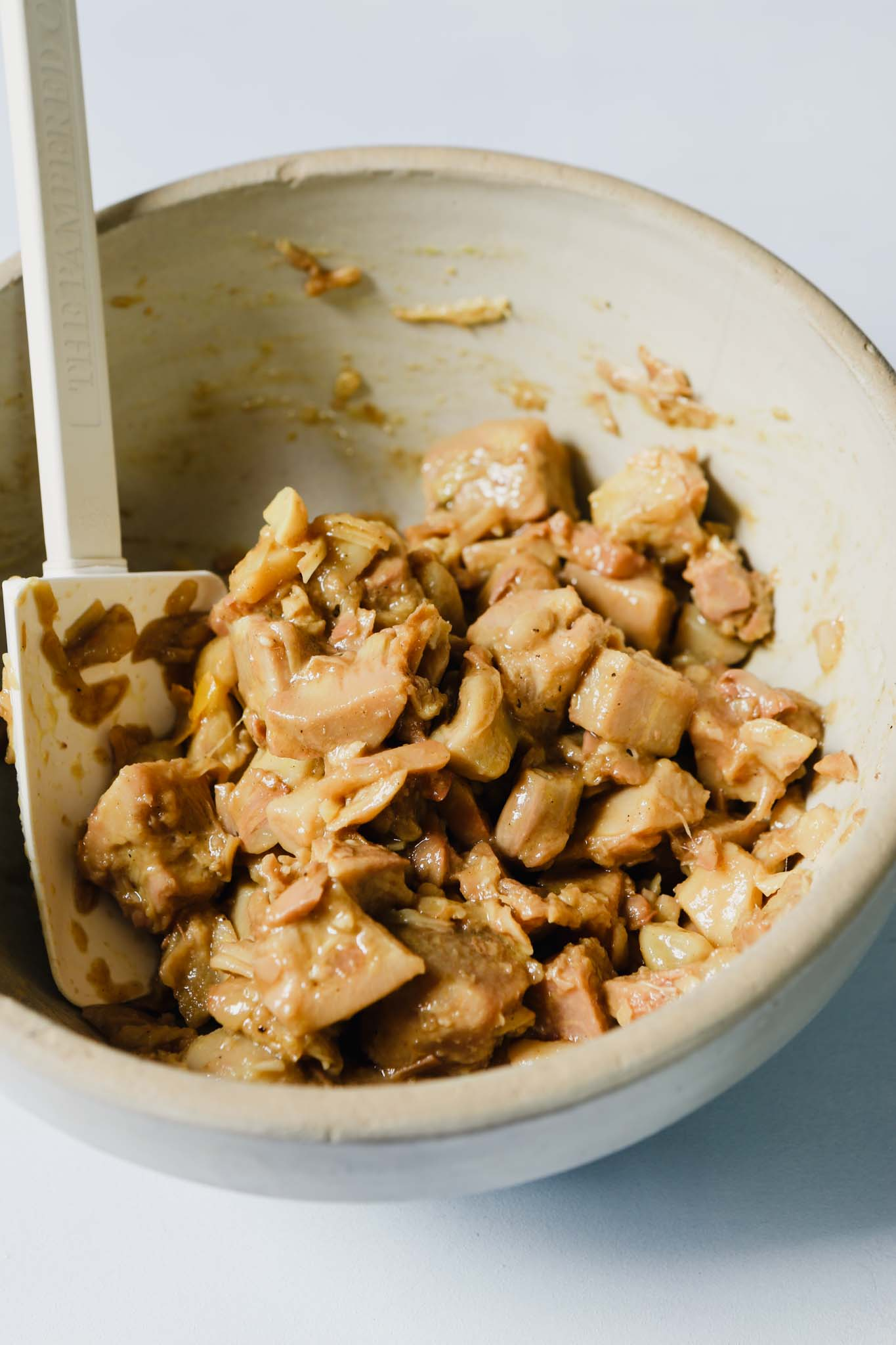 Photograph of jackfruit tossed with a banh mi sauce in a brown bowl