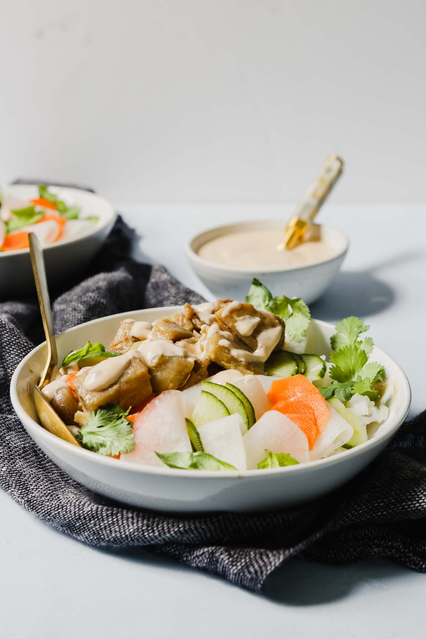 Photograph of banh mi bowls filled with rice, jackfruit, pickled vegetables, fresh herbs and a creamy sauce, set on a light blue table.
