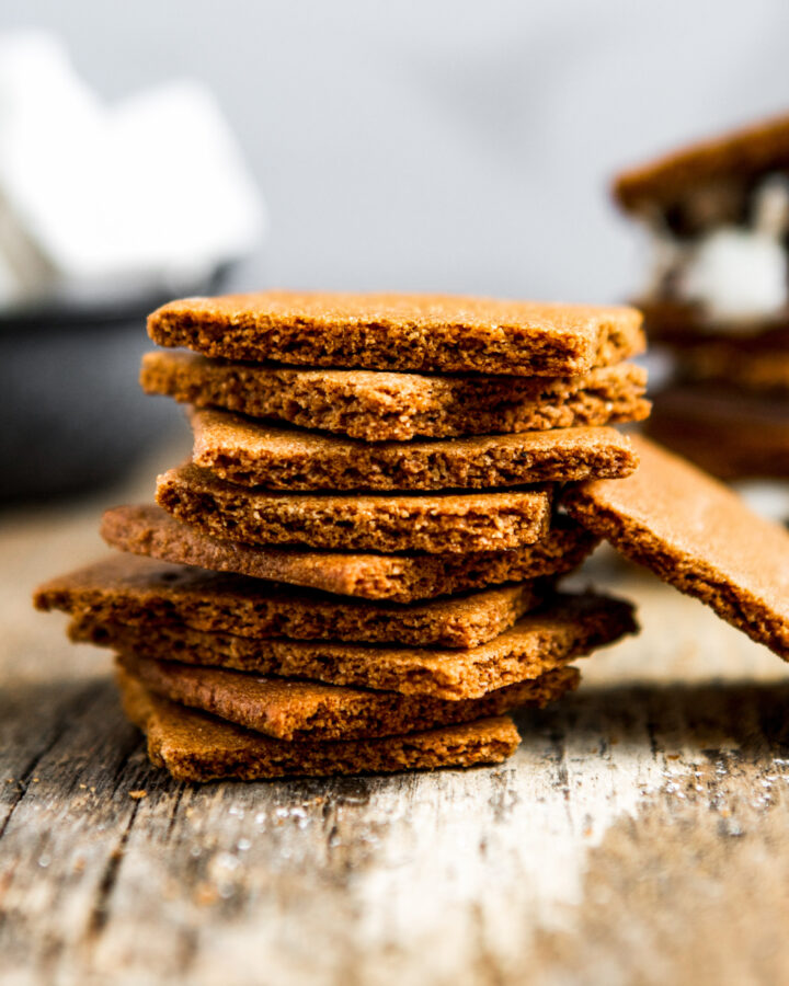 Whole wheat graham crackers stacked on a wooden table
