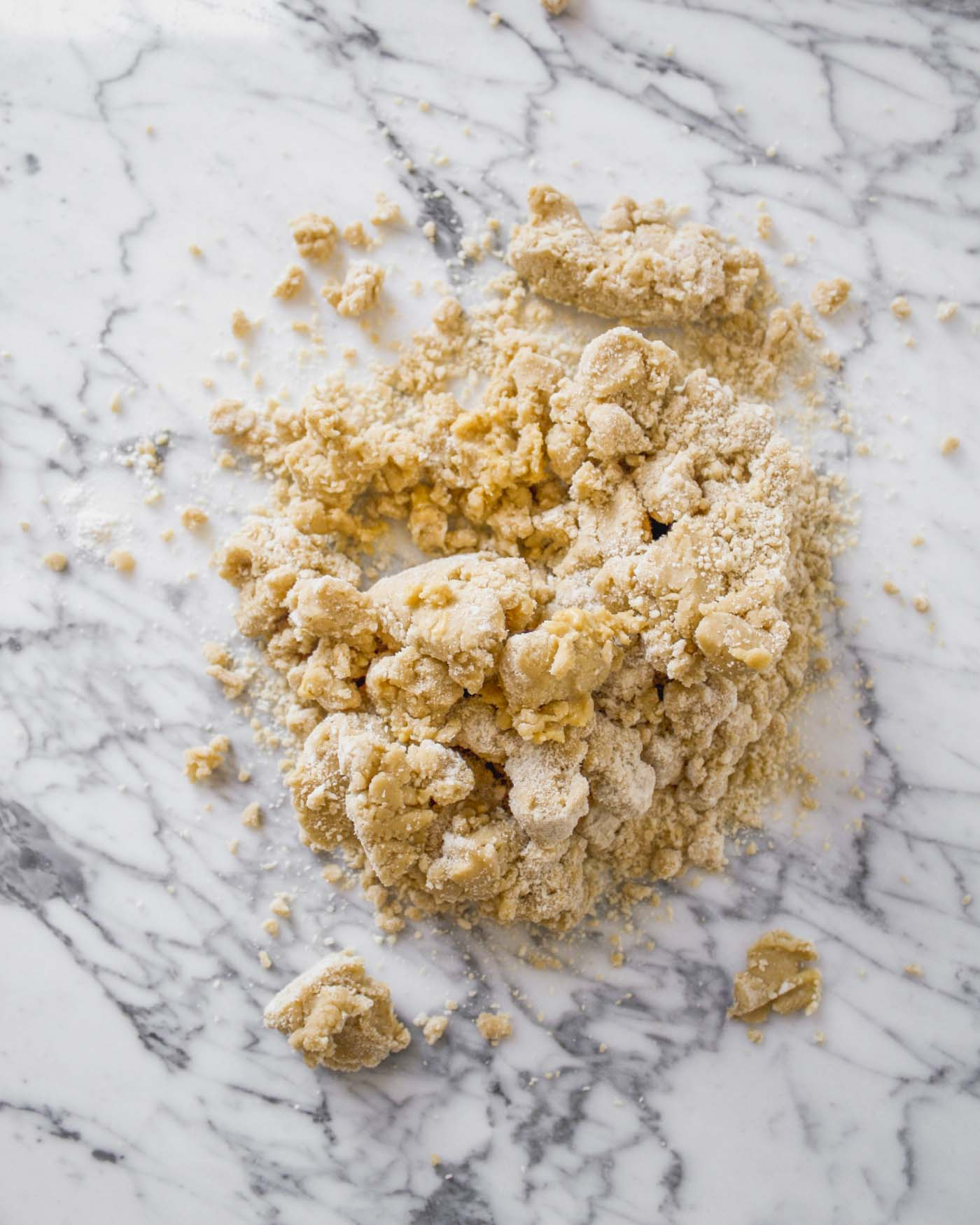 Crumbly tart dough scattered on a marble surface.