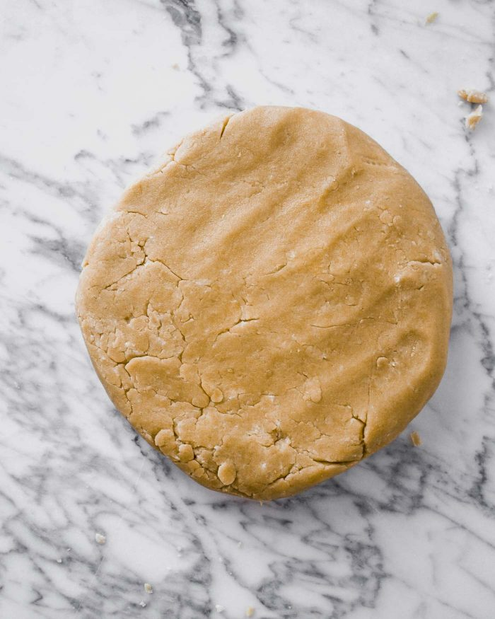 Tart dough, patted into a disk, on top of a marble surface.