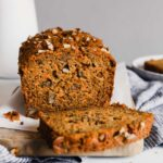 Photograph of carrot bread in a loaf pan set on a cutting board with a slice cut into it