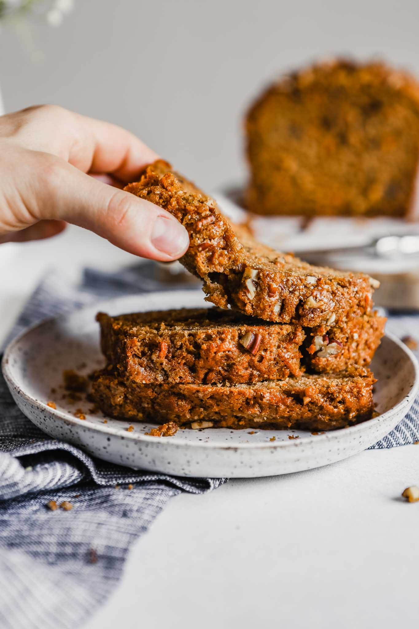 Photograph of someone picking up a slice of carrot bread off of a plate stacked with slices of bread