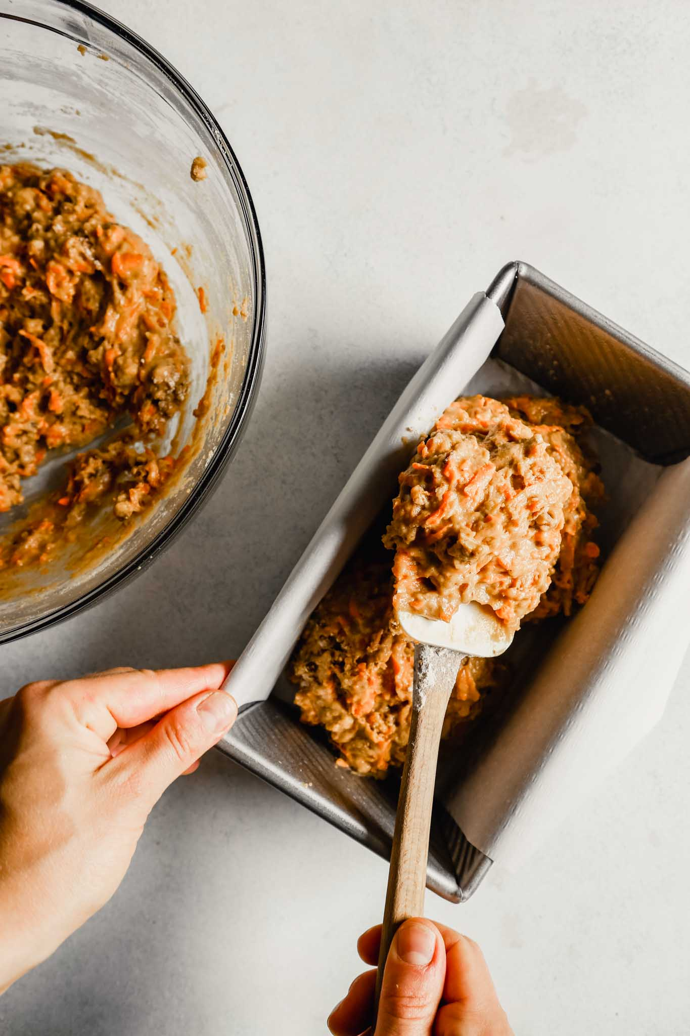 Photograph of carrot bread batter being spooned into a loaf pan