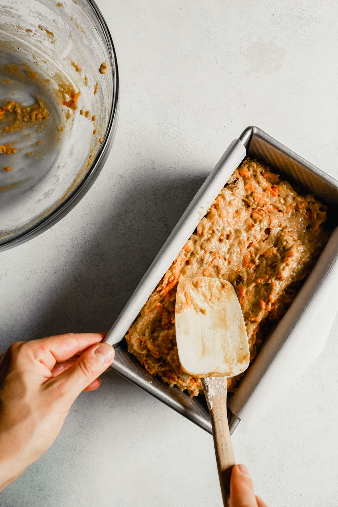 Photograph of carrot bread batter being smoothed on top in a loaf pan