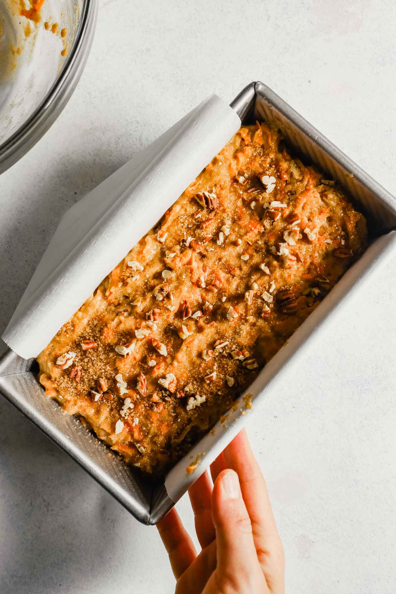 Photograph of carrot bread batter, topped with turbinado sugar and pecans, in a loaf pan