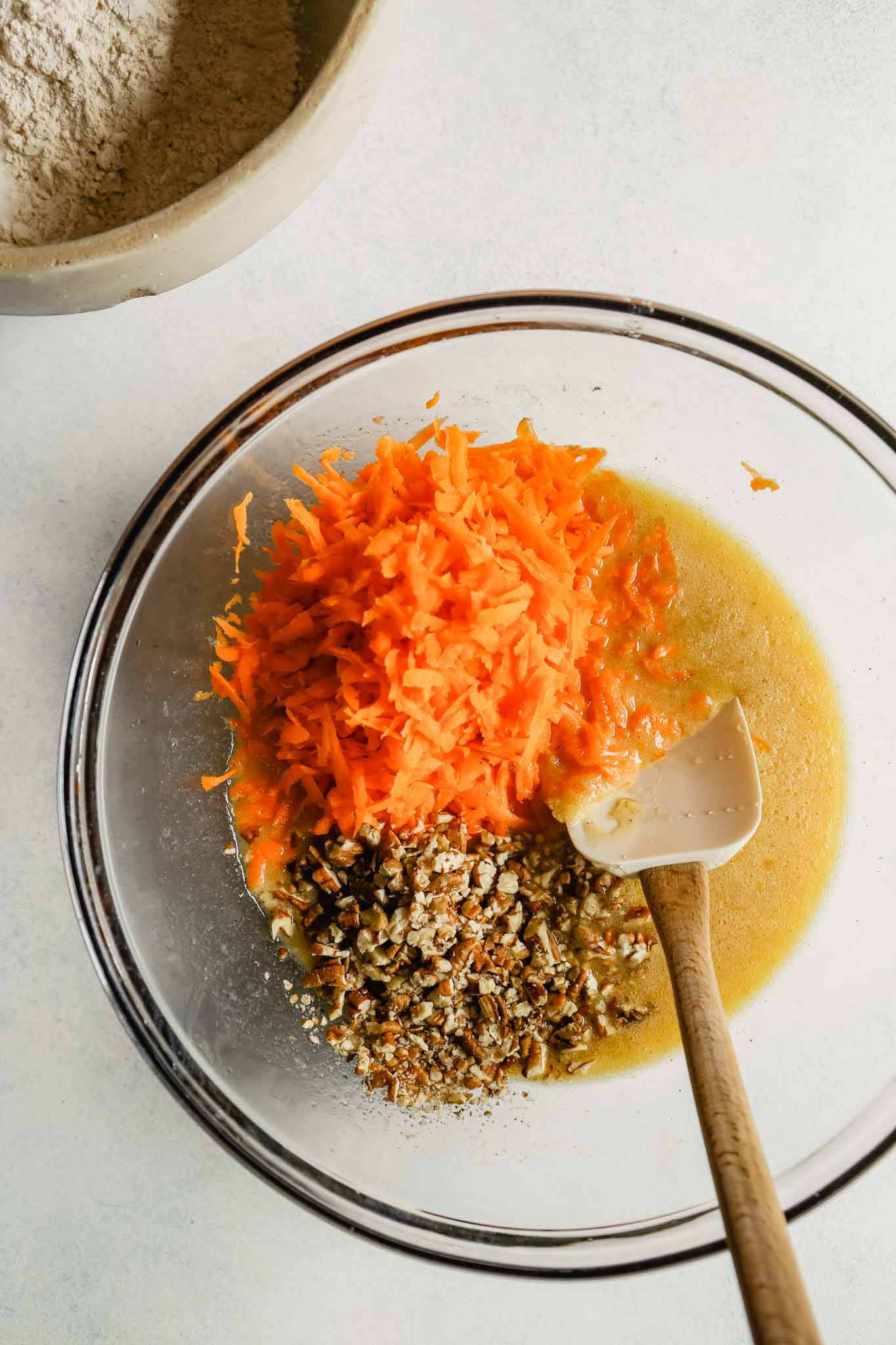 Photograph of shredded carrots and chopped pecans in a bowl with wet ingredients