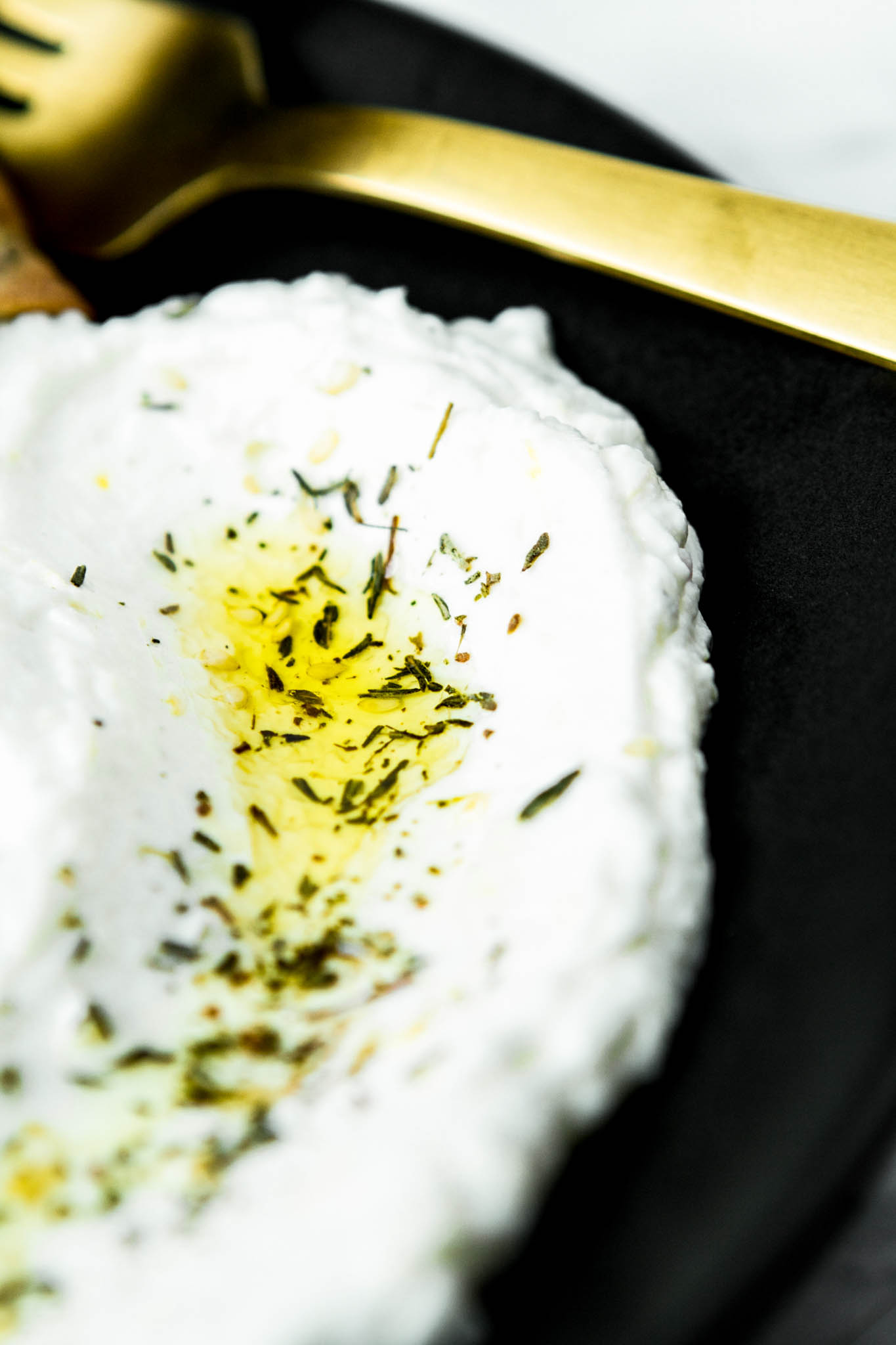 Photograph of homemade labneh spread on a plate with pita bread