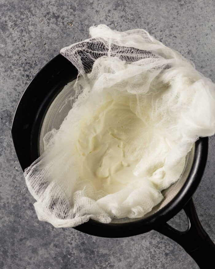 yogurt in a cheesecloth-lined sieve