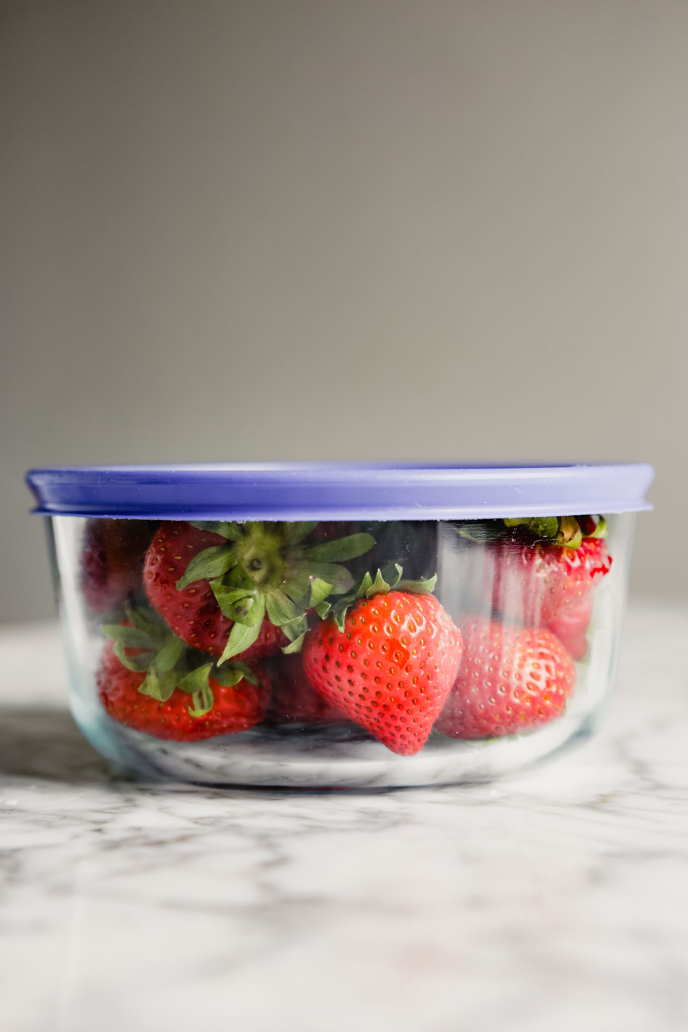 Photograph of fresh strawberries in a glass storage container with a blue lid set on a marble table